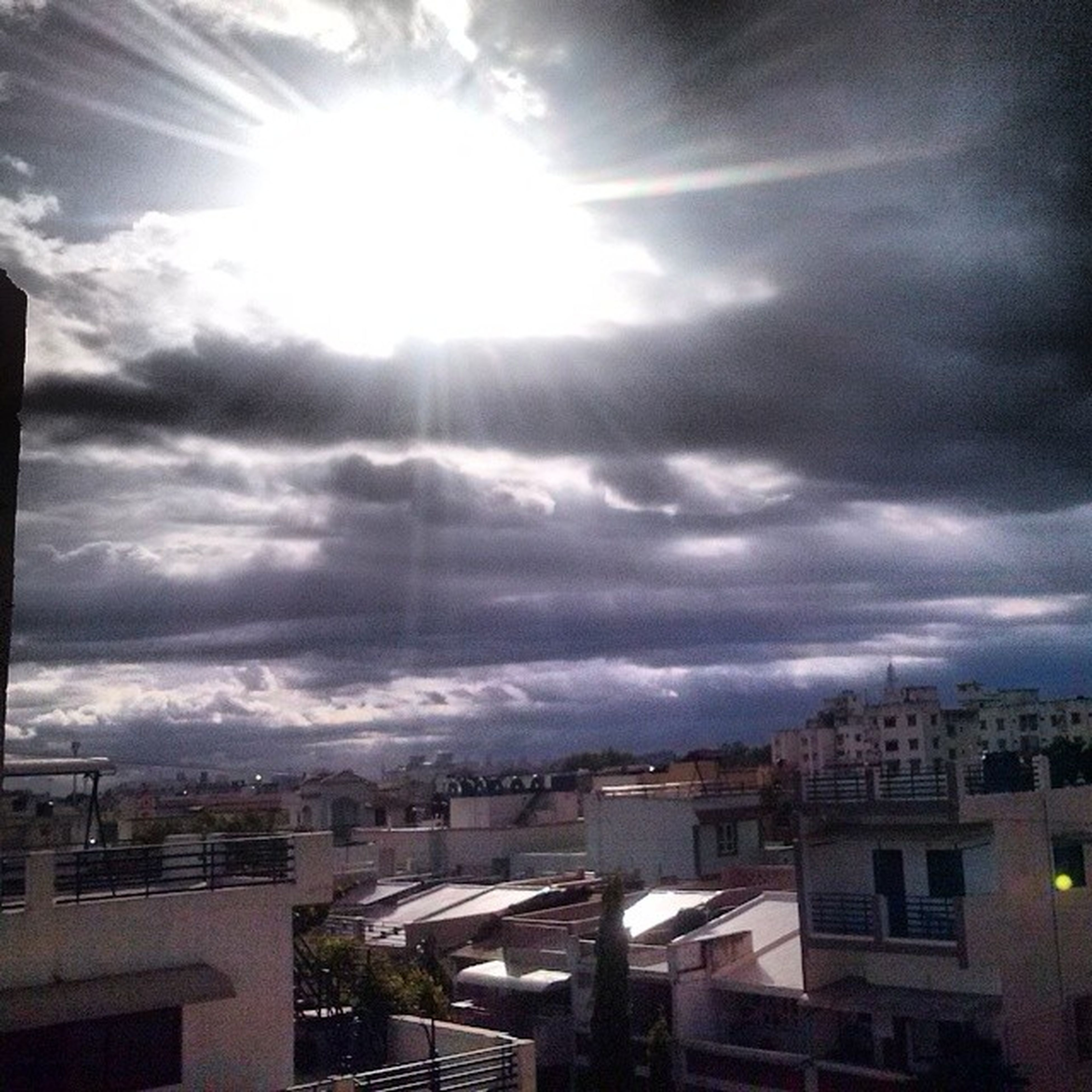 building exterior, architecture, built structure, sun, city, sky, sunbeam, cityscape, cloud - sky, sunlight, residential building, residential structure, residential district, house, lens flare, high angle view, crowded, cloud, cloudy, outdoors