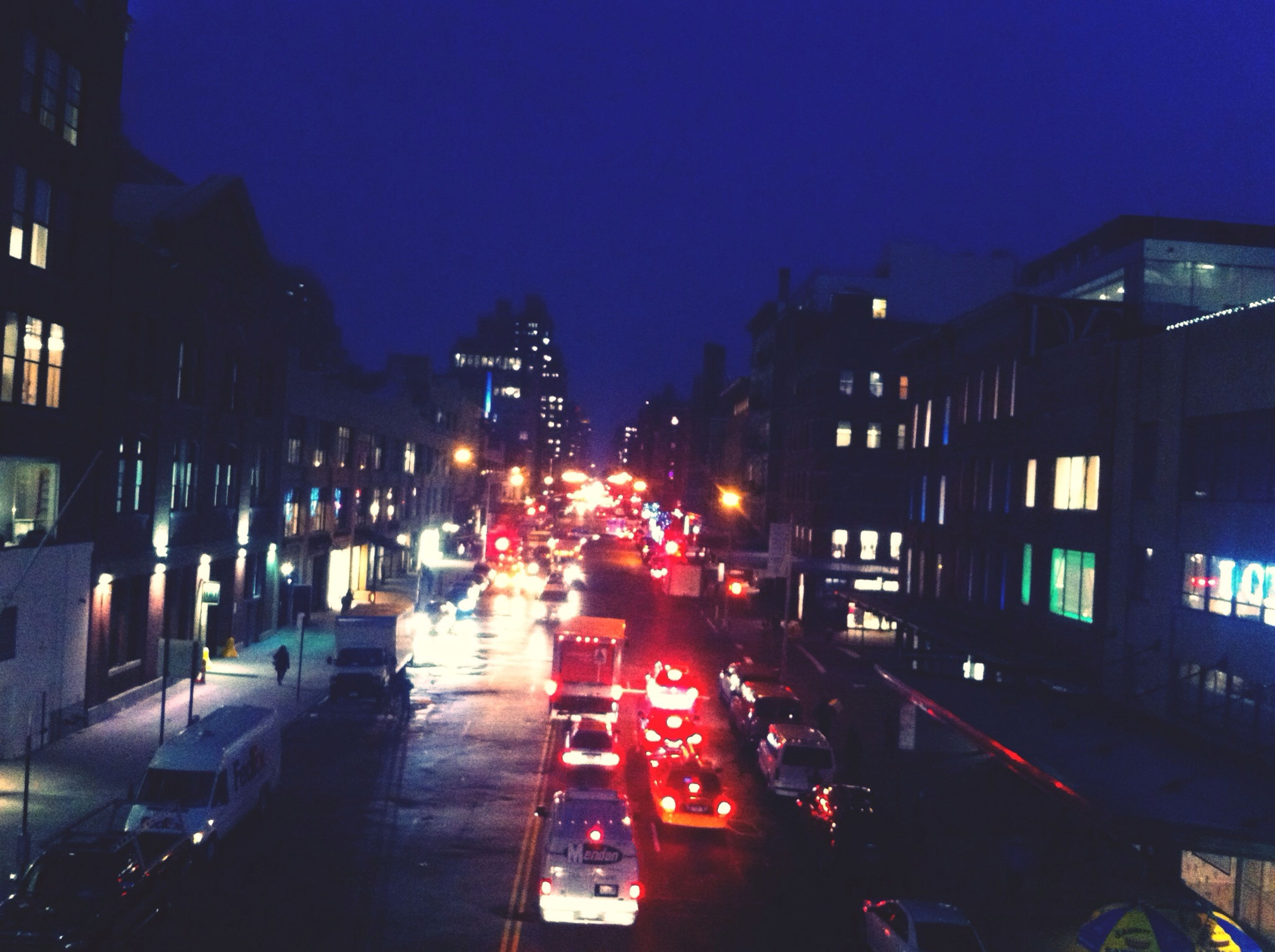 illuminated, transportation, night, mode of transport, land vehicle, building exterior, car, city, architecture, built structure, street, street light, sky, road, traffic, city life, city street, high angle view, parking, outdoors