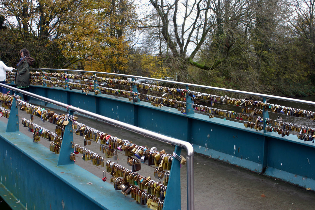 railing, bridge - man made structure, large group of people, real people, water, tree, day, outdoors, leisure activity, men, river, togetherness, footbridge, women, lifestyles, love lock, nautical vessel, nature, sky, people