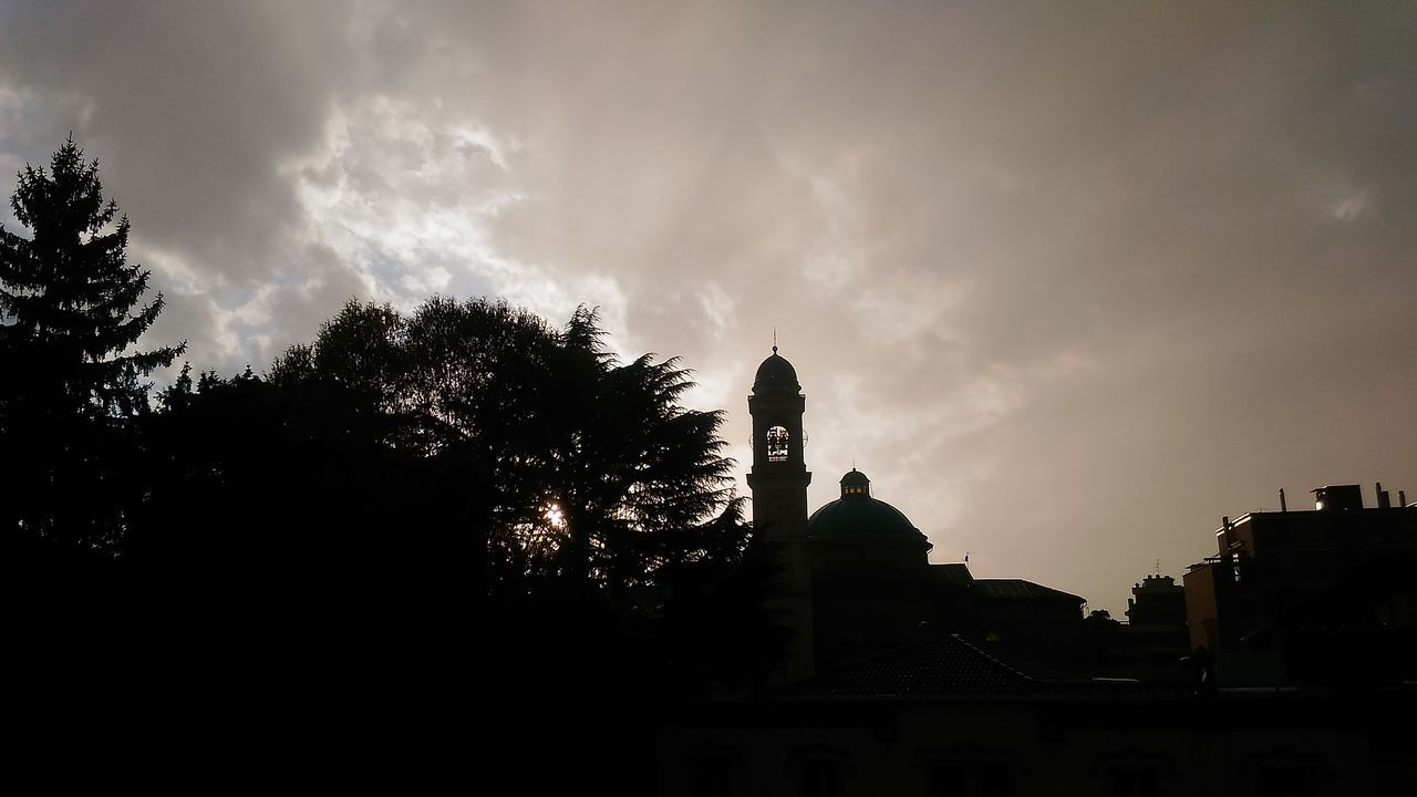 Silhouette Trees And Tower Against Cloudy Sky At Dusk