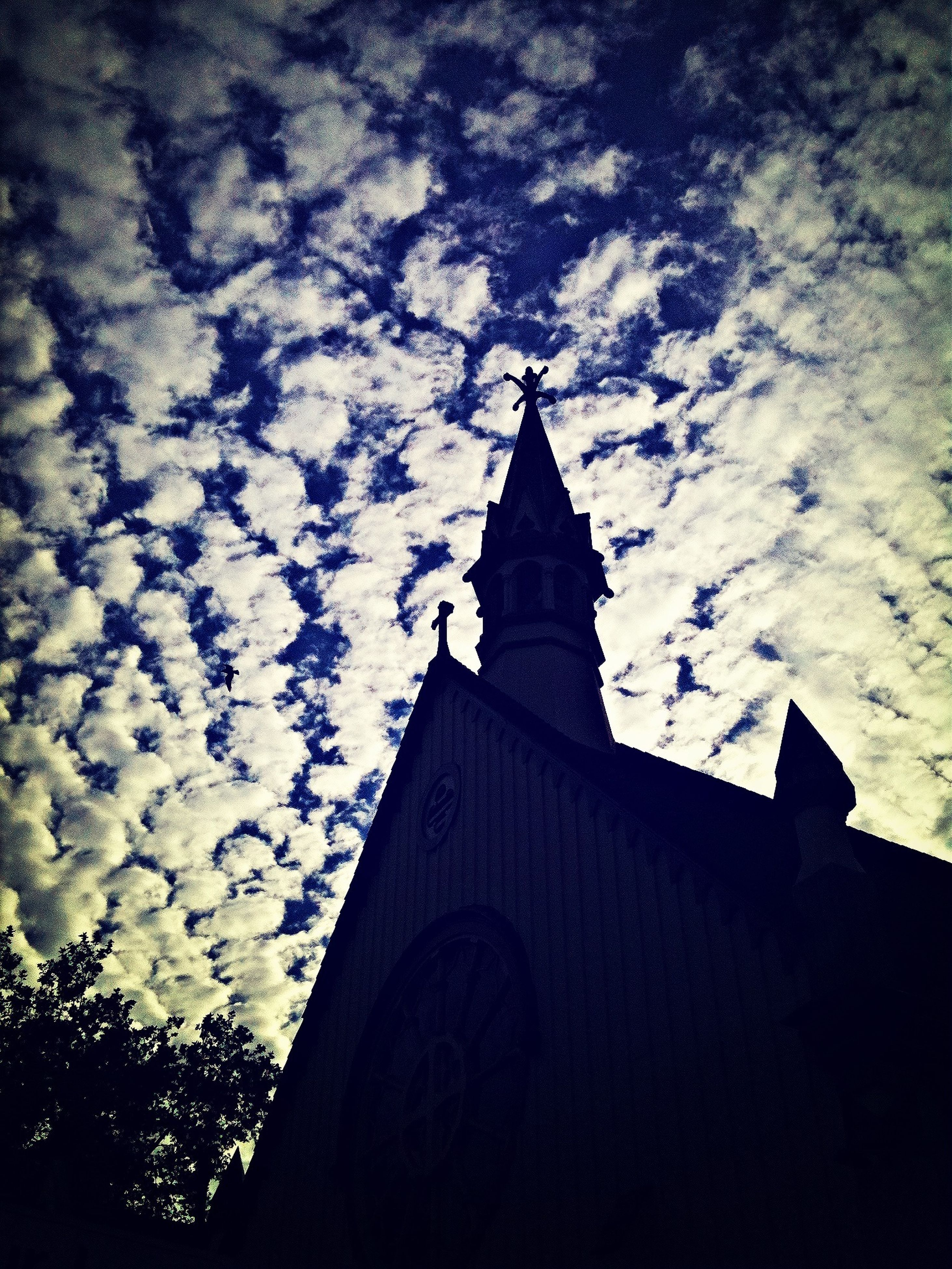 architecture, building exterior, religion, church, place of worship, built structure, spirituality, low angle view, sky, cross, cathedral, silhouette, steeple, cloud - sky, tree, tower, history, outdoors