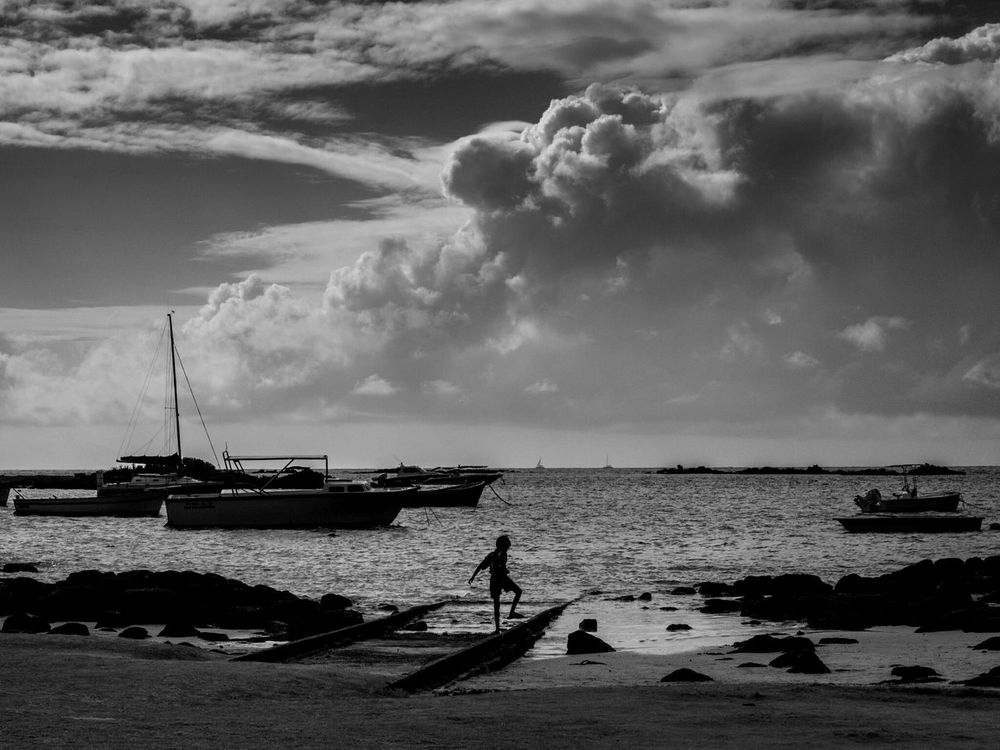 A young child plays on the beach behind the Catholic Church in Cap Malheureux Sea Water Beach Outdoors Cloud - Sky One Person Sky Real People Nautical Vessel Day Nature Beauty In Nature One Man Only People Child Cap Malheureux Noir Et Blanc Black And White Monochrome Fun