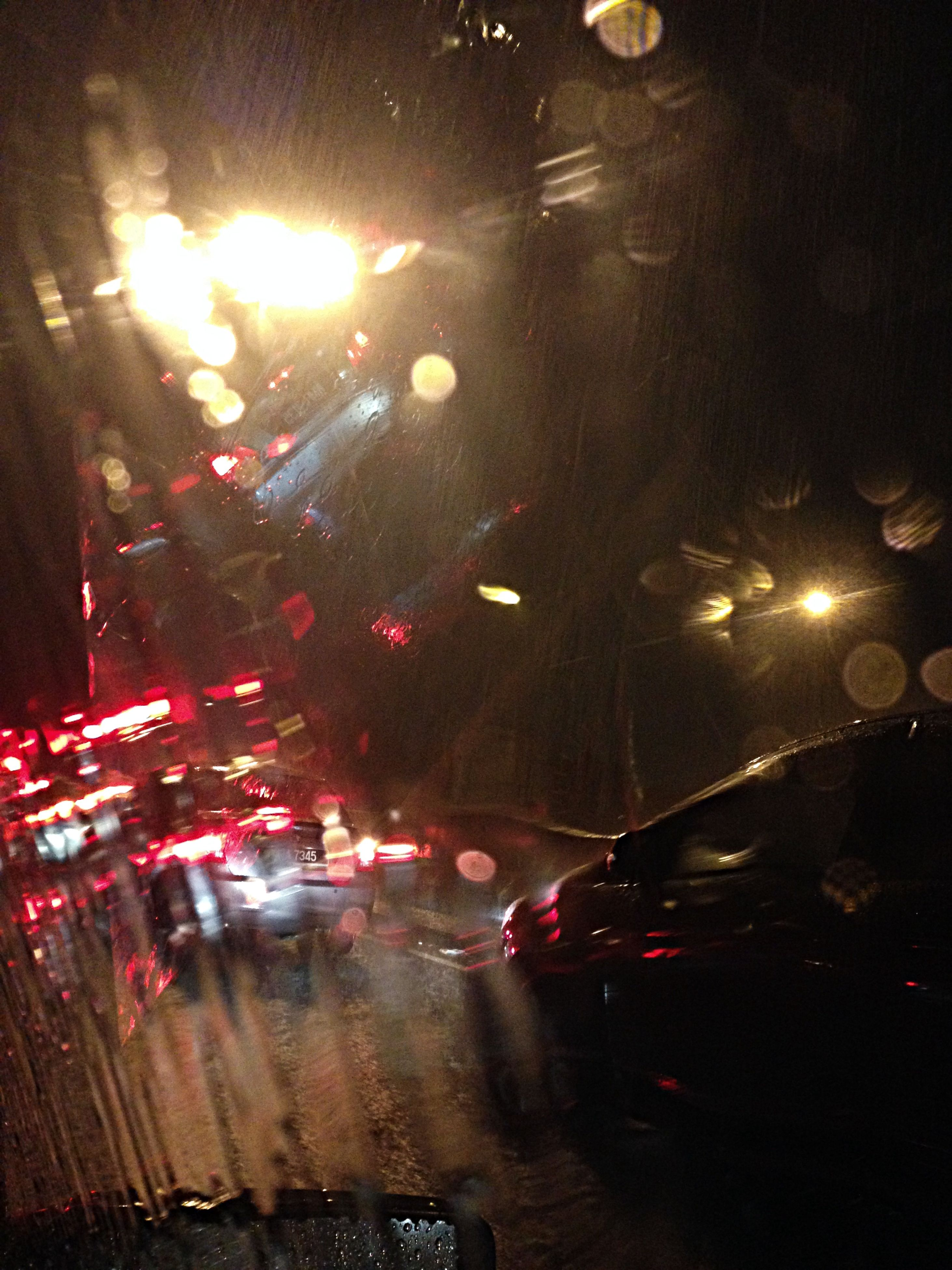 car, transportation, illuminated, land vehicle, night, mode of transport, street, road, traffic, street light, wet, city street, city, rain, on the move, headlight, tail light, city life, lighting equipment, motion