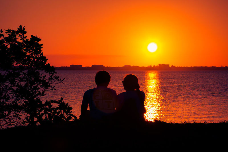 Romantic red sunset Beauty In Nature Bonding Leisure Activity Lifestyles Love Men Nature Orange Color Outdoors Real People Romantic Scenics Sea Silhouette Sitting Sky Sun Sunlight Sunset Togetherness Tranquil Scene Tranquility Tree Two People Water
