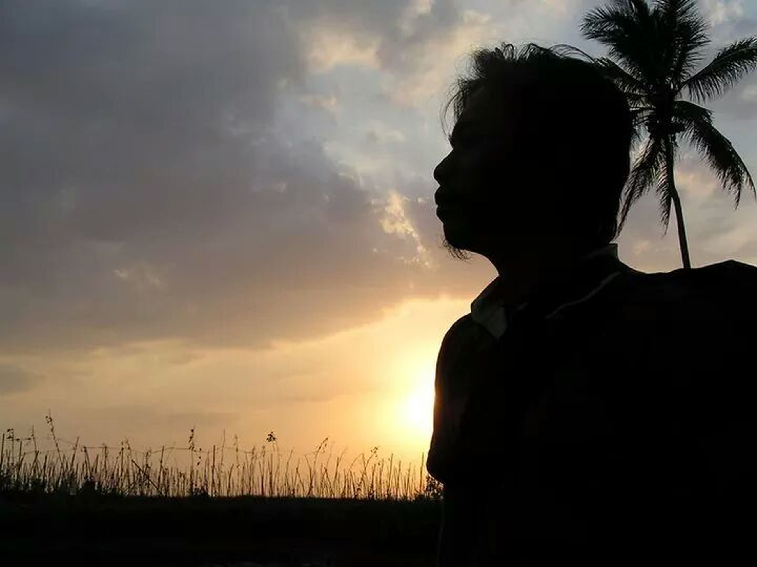 sunset, sky, silhouette, cloud - sky, nature, tranquility, lifestyles, field, beauty in nature, standing, tranquil scene, leisure activity, cloud, landscape, sun, rear view, scenics, waist up
