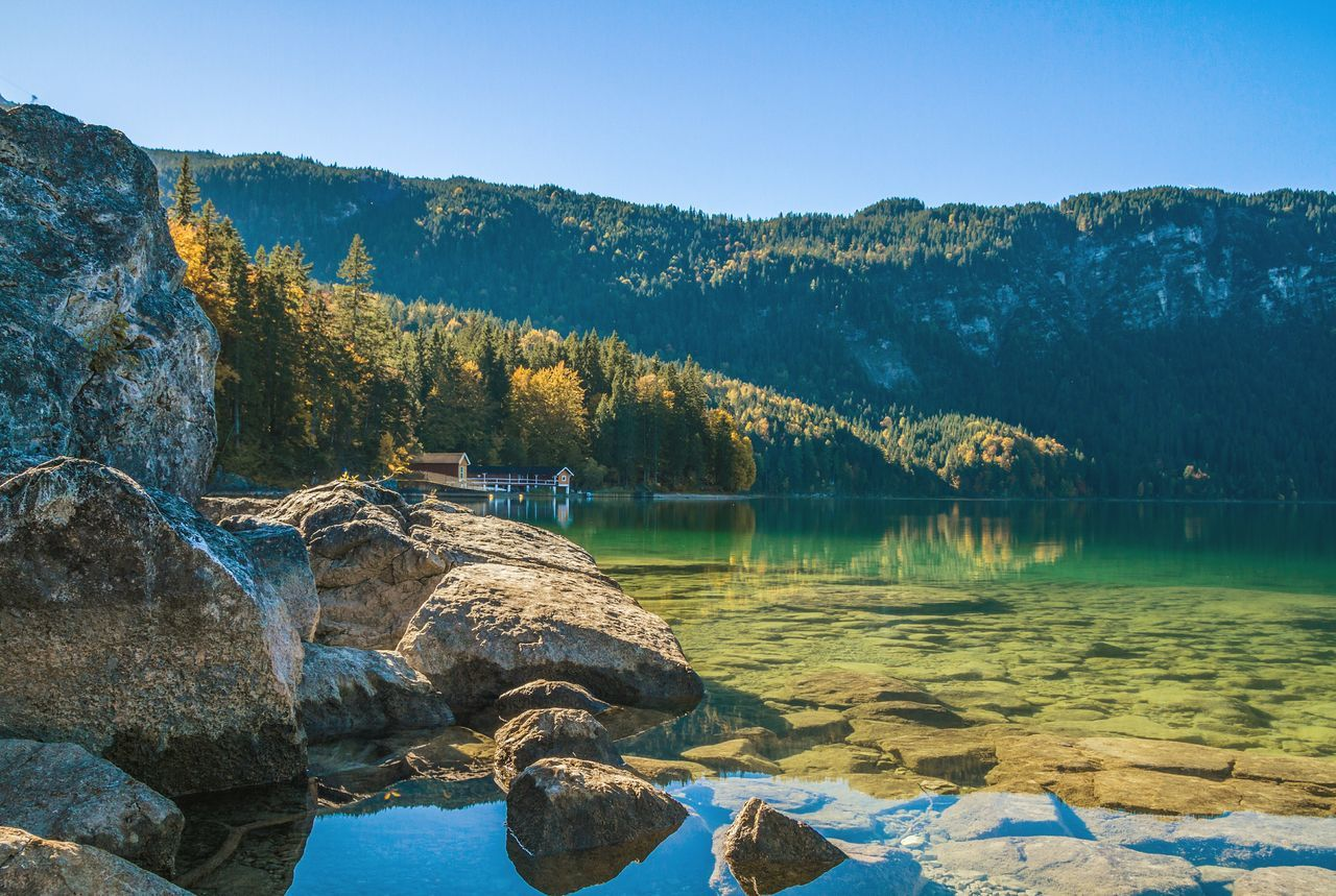 Scenic View Of Eibsee Lake By Mountain Against Clear Sky On Sunny Day