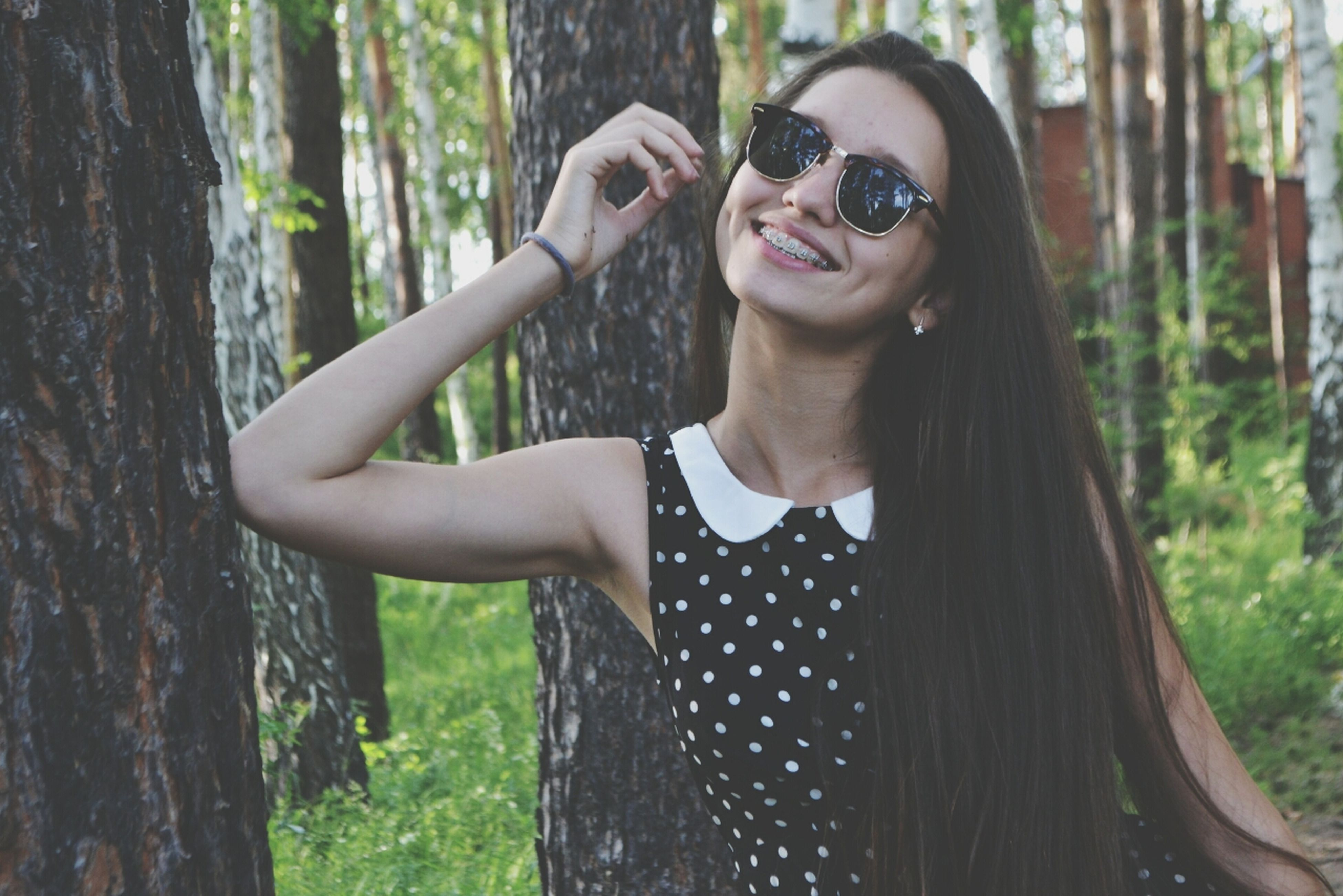 lifestyles, person, tree, young adult, leisure activity, holding, young women, casual clothing, front view, tree trunk, looking at camera, focus on foreground, portrait, smiling, waist up, forest, happiness