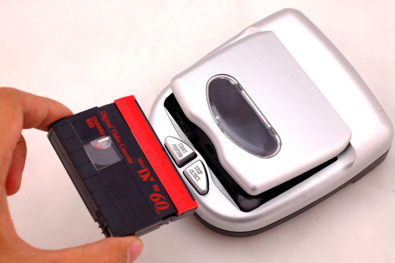 Mini Digital Video or DV Cassette and mini DV Cassette Rewinder.(Selective focus) CASSETTE REWINDER; REWINDER; Back; Background; Backup; Black; Camcoder; Camcorder; Camera; Cassette; Cinema; Digital; Digitally; Disk; Display; Dv; Electronics; Equipment; Film; Hand; Isolated; Magnetic; Media; Mini; Mini-dv; Minute; Movie; Multimedia; Ob Video;