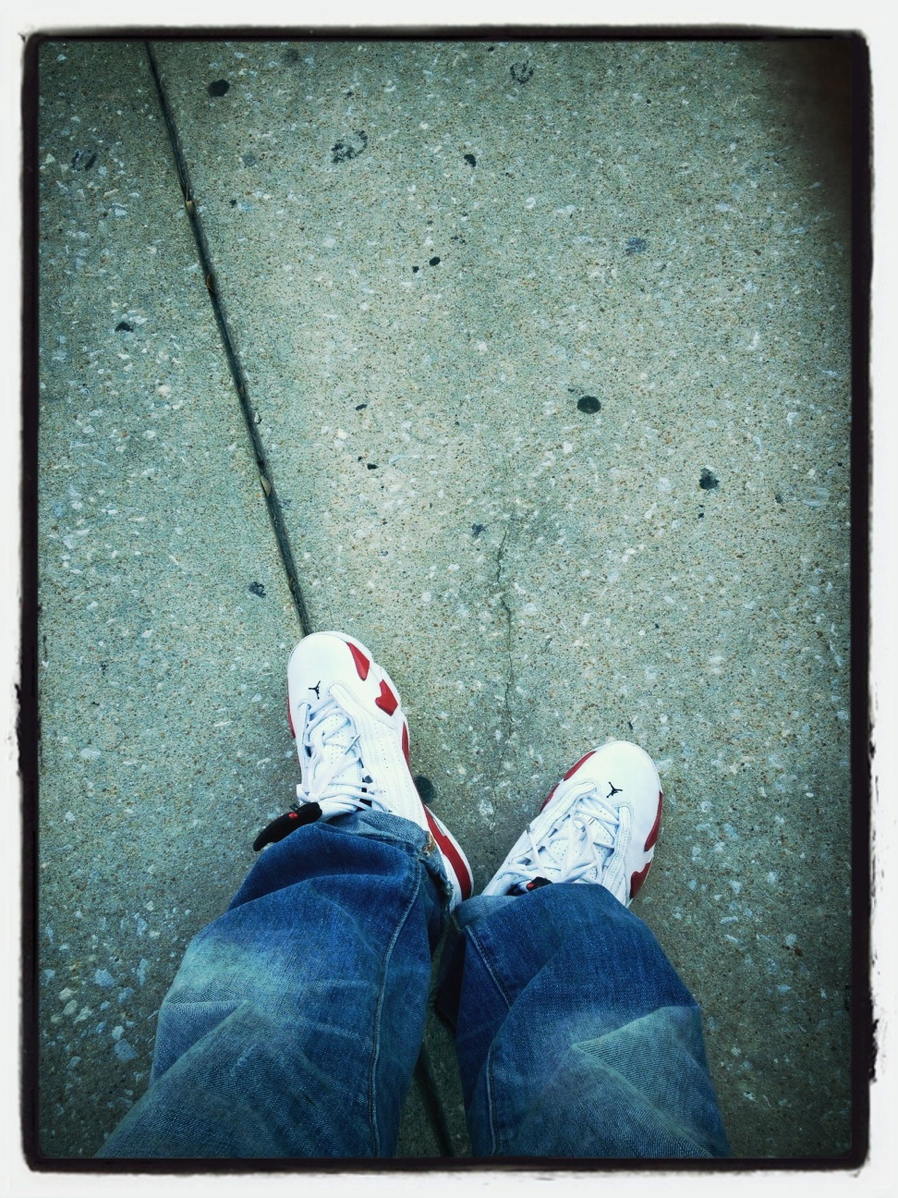low section, person, shoe, transfer print, personal perspective, standing, lifestyles, high angle view, jeans, men, auto post production filter, footwear, human foot, leisure activity, casual clothing, street, directly above
