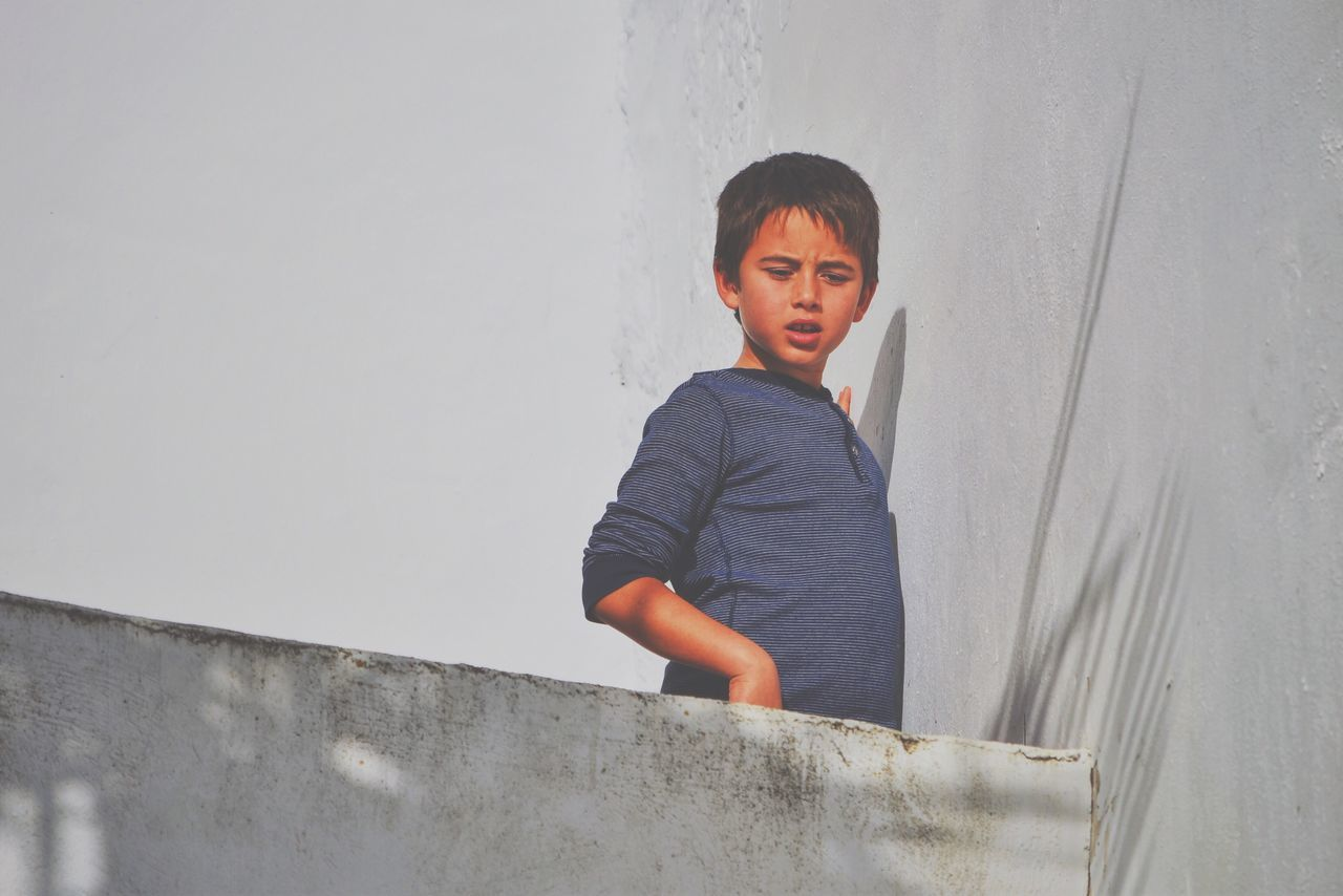 Low Angle View Of Boy Standing At Building Terrace