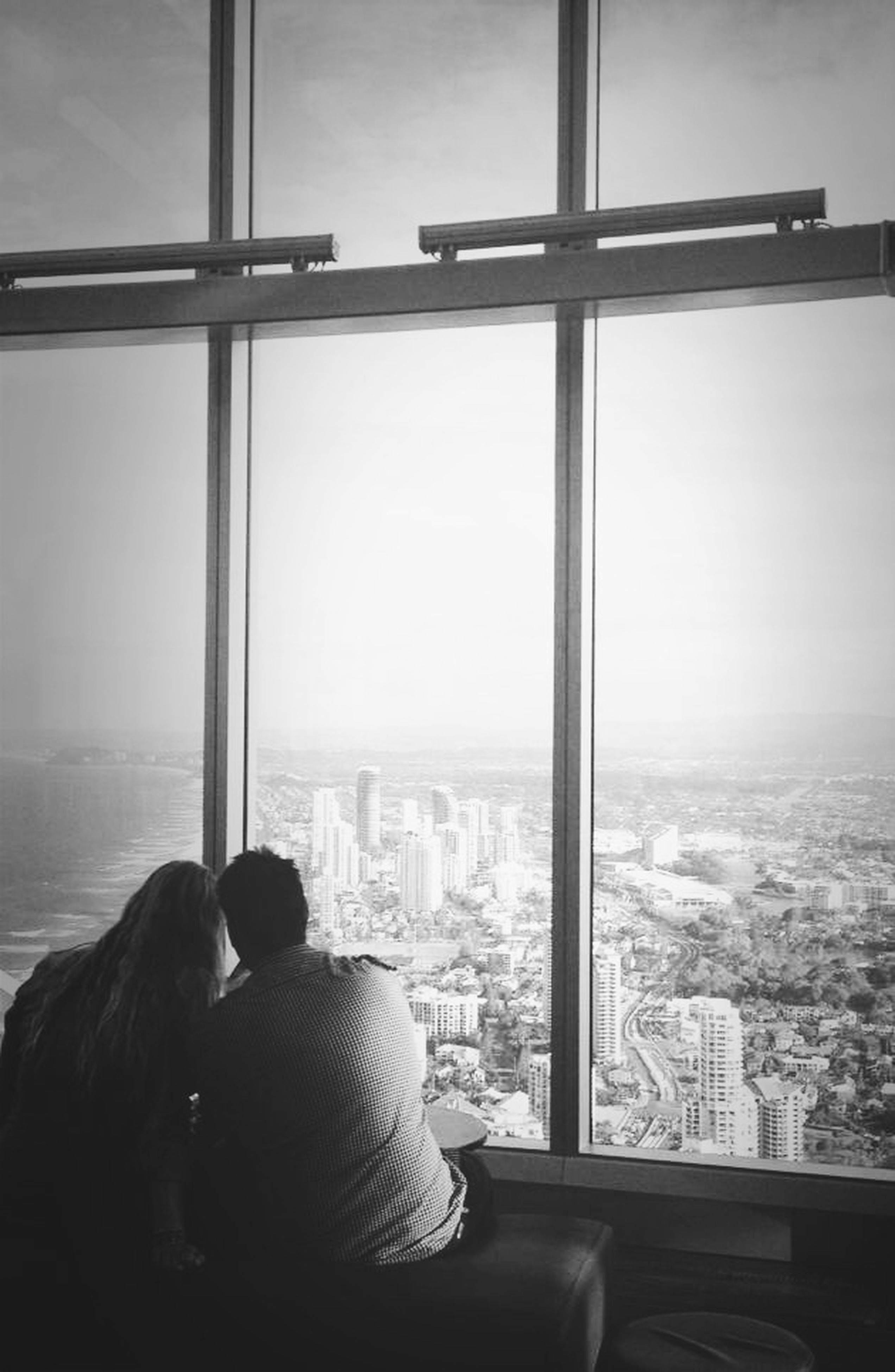city, cityscape, architecture, indoors, built structure, window, glass - material, building exterior, skyscraper, sky, transparent, modern, looking through window, tower, tall - high, city life, capital cities, sunset, rear view, travel destinations