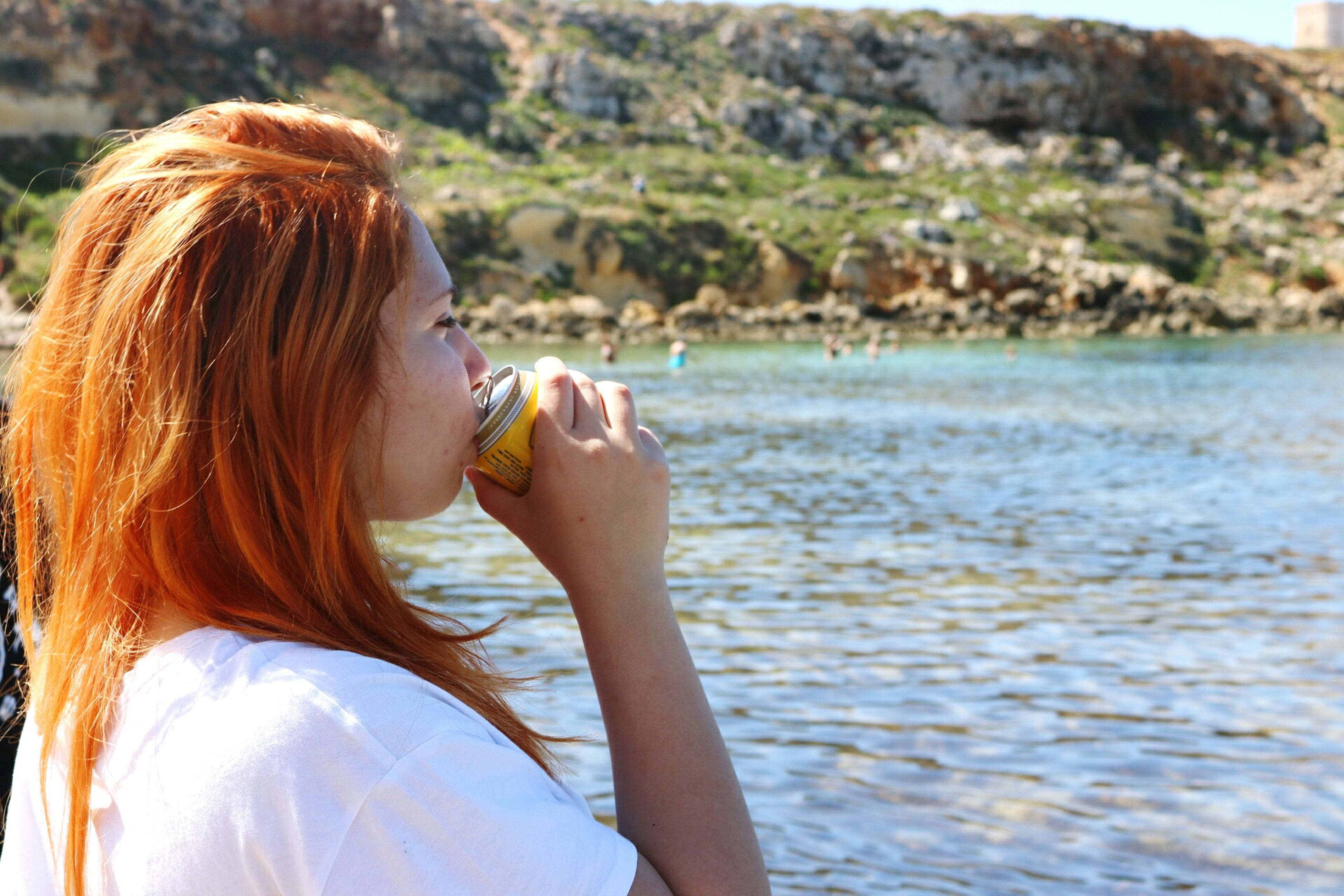 redhead, one person, real people, water, young women, young adult, leisure activity, outdoors, side view, food and drink, lifestyles, women, day, sea, nature, beach, eating, beauty in nature, one young woman only, close-up, adult, people