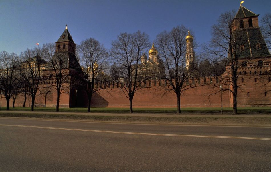 Outside the Russian Kremlin in Moscow. It is a sunny day in late winter. There is no longer snow on the ground but it is still very cold and spring feels a long way off. The lack of foliage on the trees allows us to see through to the golden onions of the Russian Kremlin Churches - the Assumption and Annunciation Cathedrals (left) and Archangel's Cathedral (centre). The Ivan the Great Bell Tower - said to mark the exact centre of Moscow - is the tall golden dome on the right. In Russia, the word Kremlin implies a medieval, inner-city fortress. In earlier times it would have probably meant a fortified town, or town surrounded by a wall. There are therefore a number of kremlins in Russia; although when we talk about The Kremlin, we usually mean where the workings of power take place in the Russian capital, Moscow. As well as being the official working residence of the Russian President, the Moscow Kremlin also houses Russia's main museum. The outer red brick wall of the Moscow Kremlin was built at the turn of the 15th and 16th centuries; replacing the earlier fire hazard, made of wood. The tower on the left is The Secret (Tainitskaya) Tower and to the left of that is The Grand Kremlin Palace. http://pics.travelnotes.org/ Architecture Blue Sky Cathedrals  Fortress Ivan The Great Bell Tower Kremlin Kremlin Palace Late Winter Michel Guntern Moscow No Leaves No People Palace Red Brick Wall Russia Russian Russian Kremlin Street Scene Sunny Day The Kremlin Tourist Attraction  Travel Travel Photography Travel Photos Travel Pics