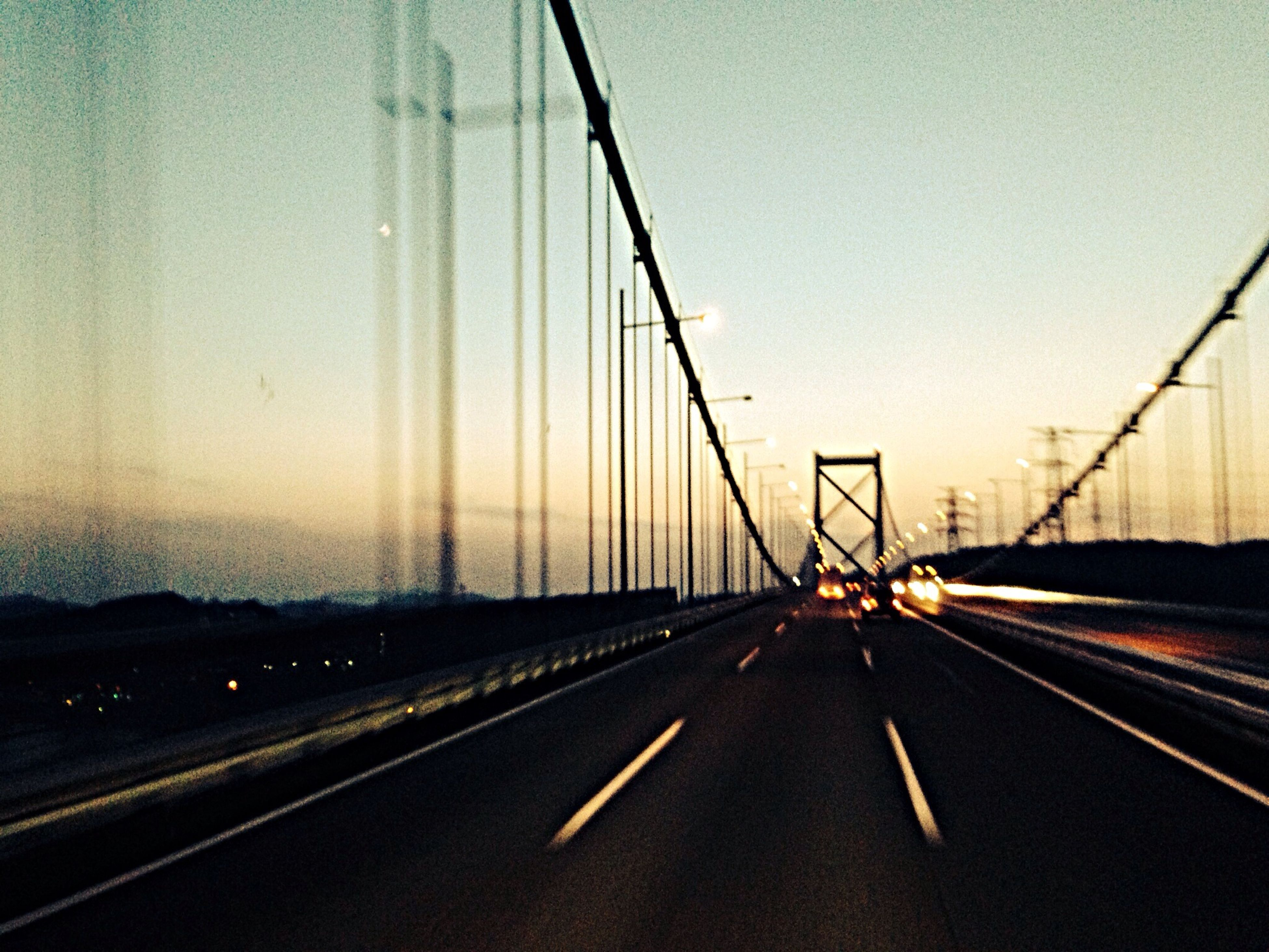 transportation, road, the way forward, road marking, connection, diminishing perspective, clear sky, mode of transport, car, vanishing point, sunset, sky, land vehicle, highway, on the move, travel, suspension bridge, street light, bridge - man made structure, dusk