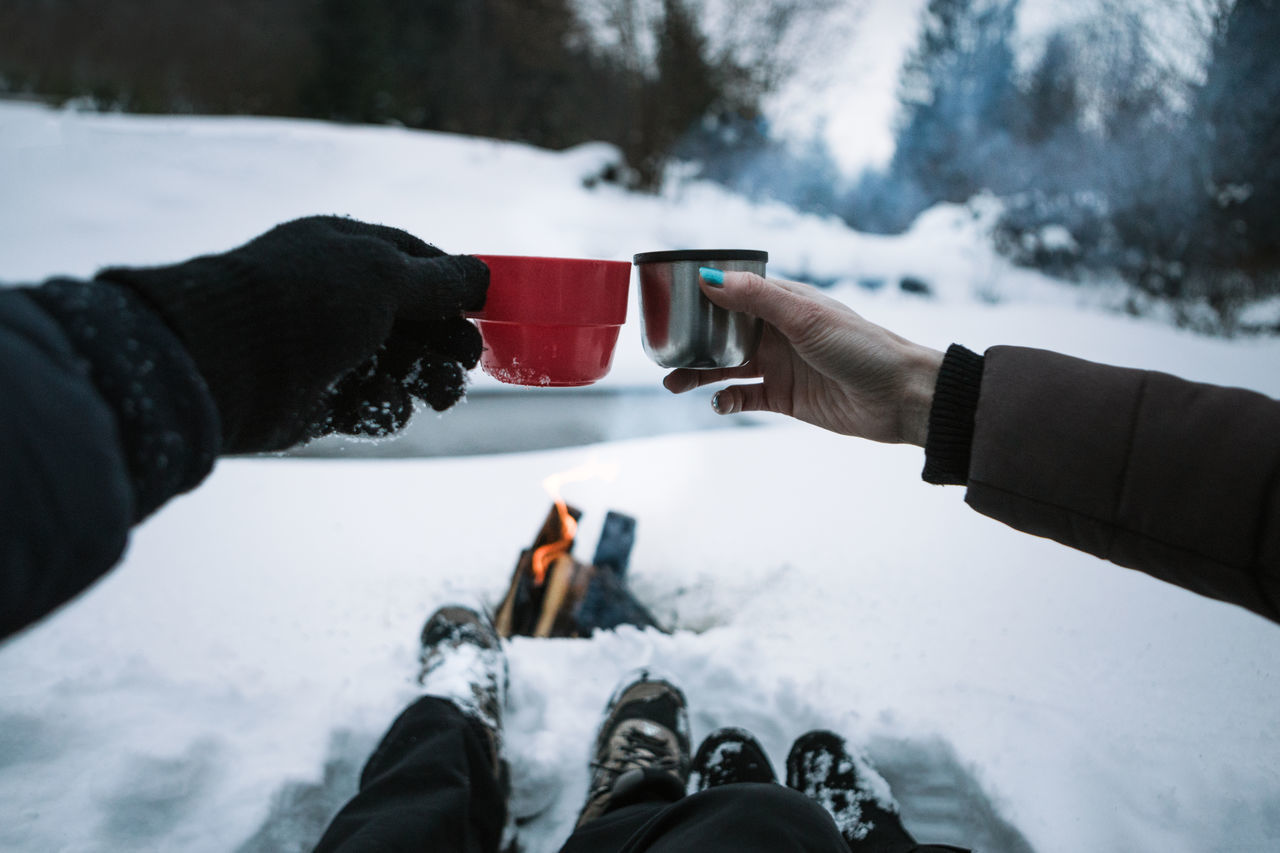 winter, snow, cold temperature, human hand, human body part, real people, personal perspective, holding, weather, cold, ice, frozen, outdoors, drink, leisure activity, nature, food and drink, lifestyles, day, warm clothing, men, mountain, women, low section, close-up, friendship, freshness, people