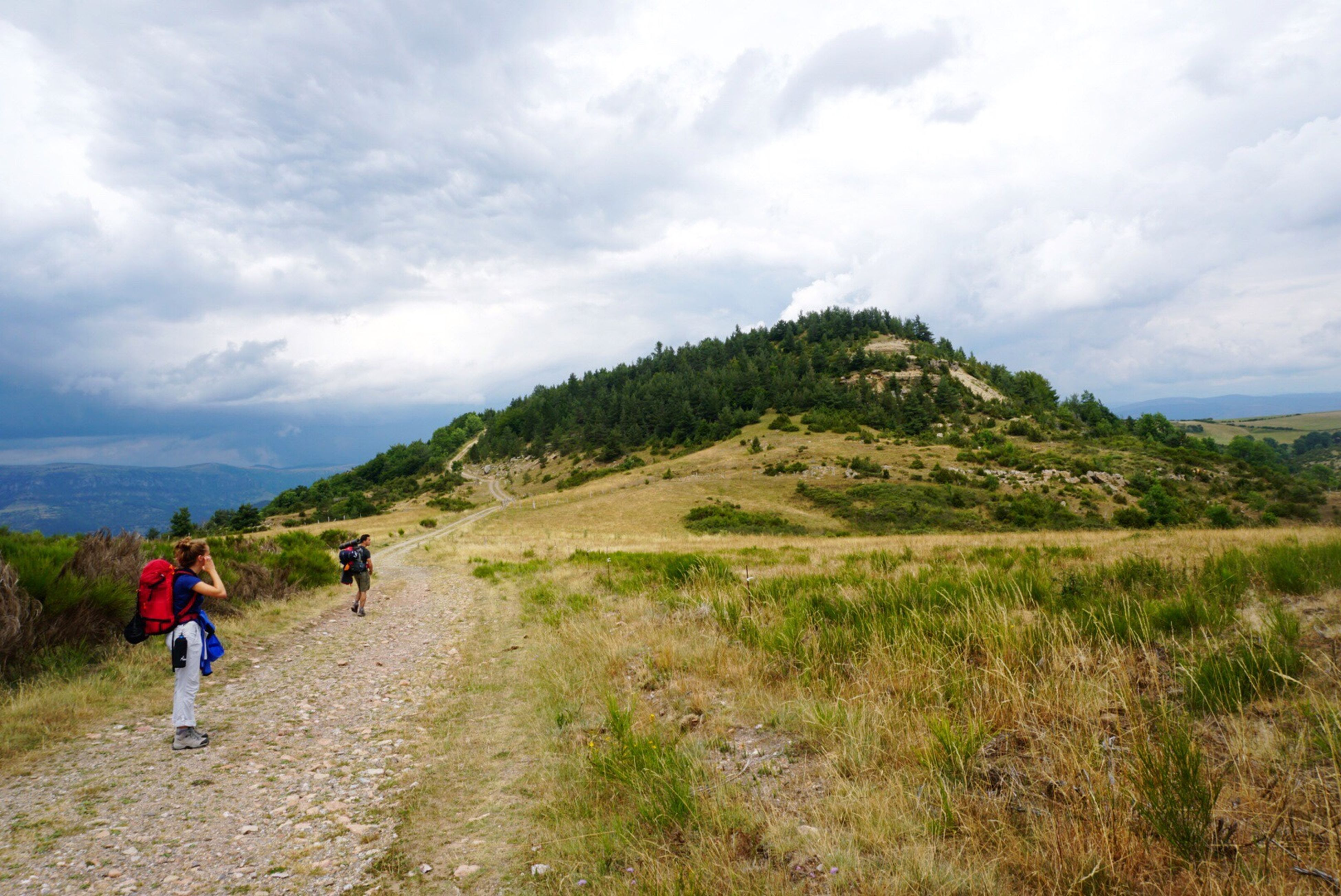 sky, nature, mountain, cloud - sky, walking, grass, landscape, scenics, backpack, hiking, rear view, beauty in nature, real people, tranquil scene, day, tranquility, adventure, leisure activity, men, outdoors, lifestyles, full length, friendship, people