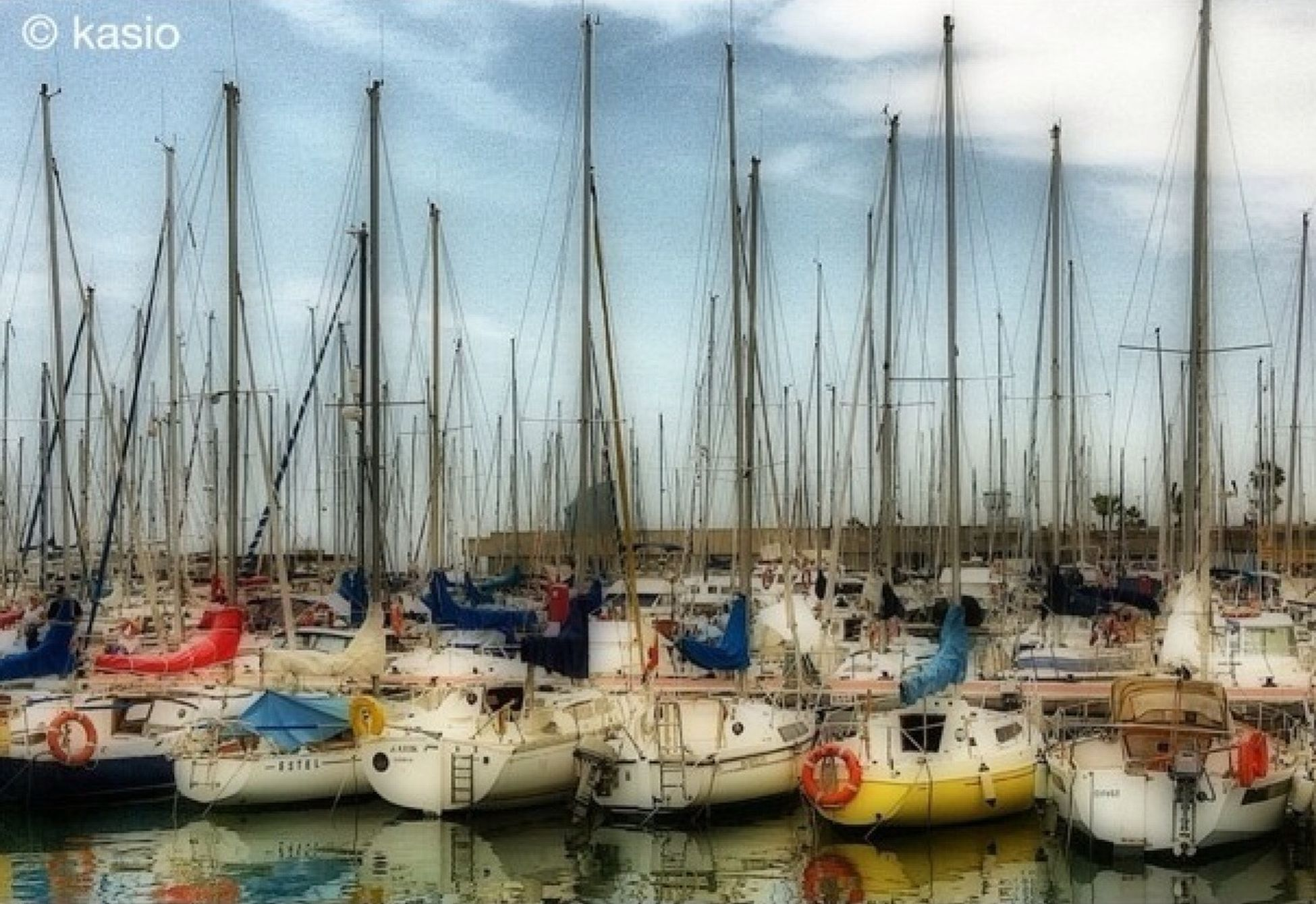 nautical vessel, moored, boat, transportation, mode of transport, harbor, water, mast, large group of objects, abundance, in a row, side by side, sailboat, group of objects, sky, reflection, waterfront, day, no people, outdoors