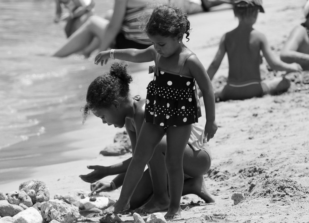 childhood, real people, full length, sand, beach, togetherness, leisure activity, girls, boys, elementary age, outdoors, day, fun, focus on foreground, happiness, lifestyles, vacations, playing, young women, water, young adult, animal themes, people