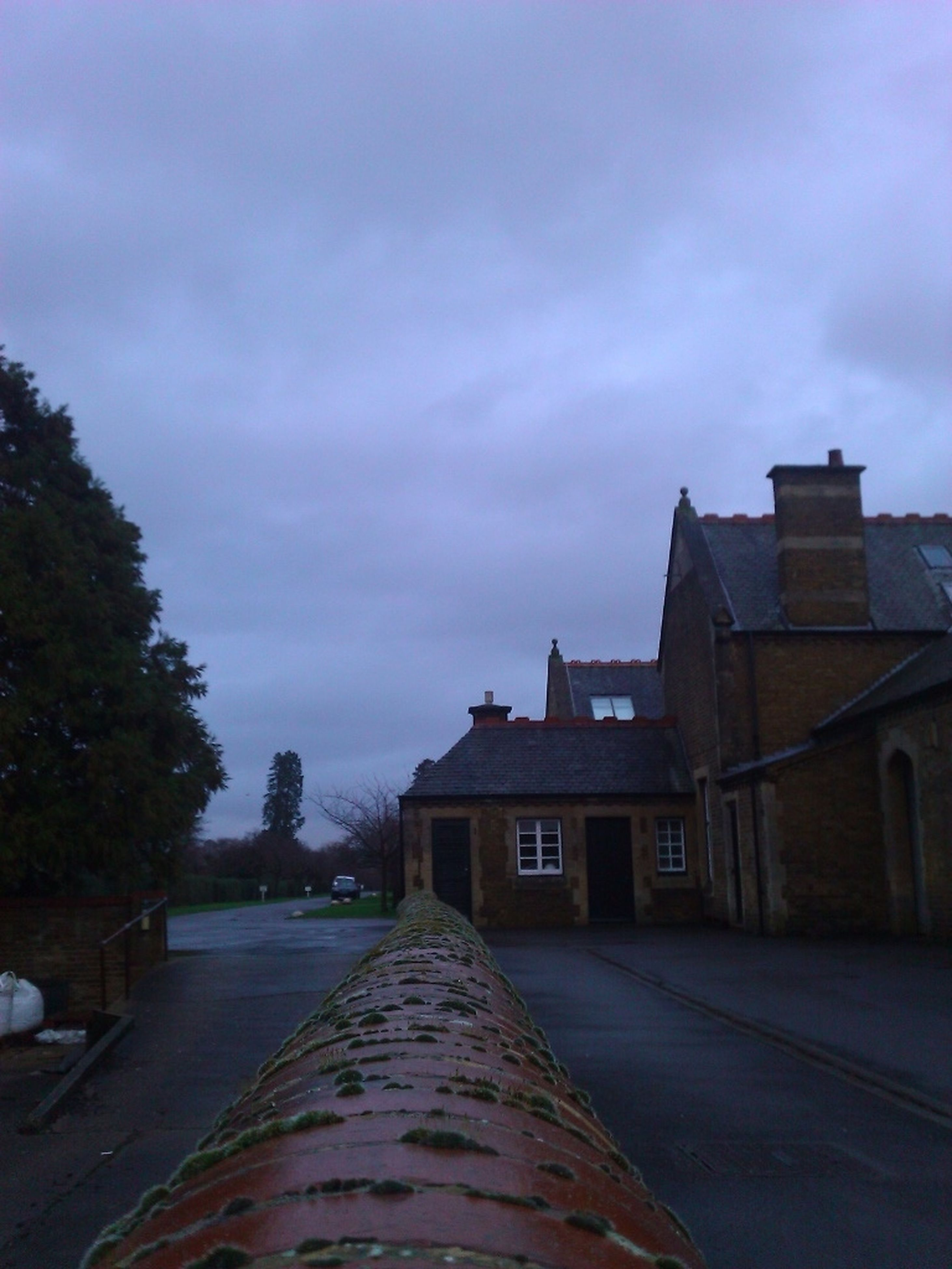 building exterior, the way forward, architecture, built structure, sky, cloud - sky, house, street, diminishing perspective, road, walkway, cloudy, residential structure, cloud, vanishing point, cobblestone, empty, outdoors, footpath, residential building