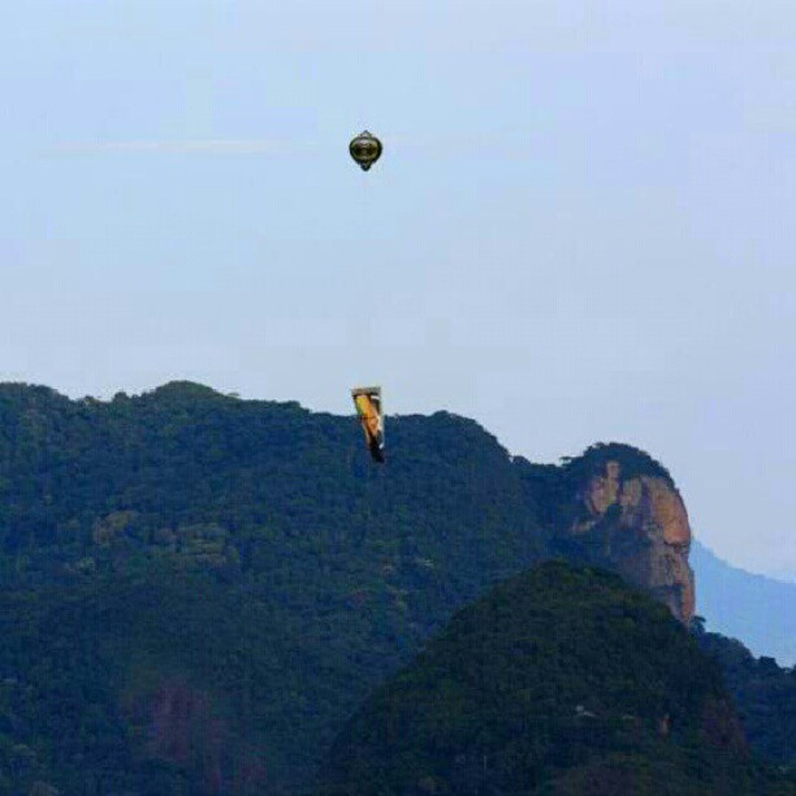 flying, mid-air, hot air balloon, clear sky, mountain, adventure, copy space, low angle view, parachute, scenics, sky, tranquility, tranquil scene, paragliding, beauty in nature, nature, transportation, leisure activity, extreme sports