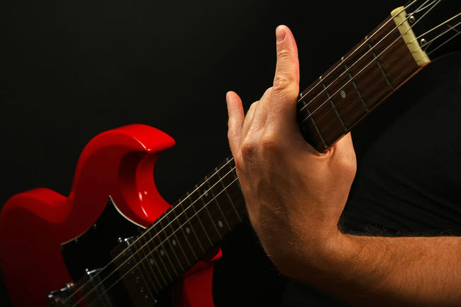 Work hard and rock hard! Man holding red electric guitar and showing Devil's horns, famous rock sign gesture Black Background Devil Horns Devilhorns Electric Guitar Gesture Gibson Guitar Guitarist Hand Heavy Metal Lifestyles Man Music Musical Equipment Musical Instruments Musician Playing Red Rock Rock'n'Roll Rocker Rocknroll Sg Sign