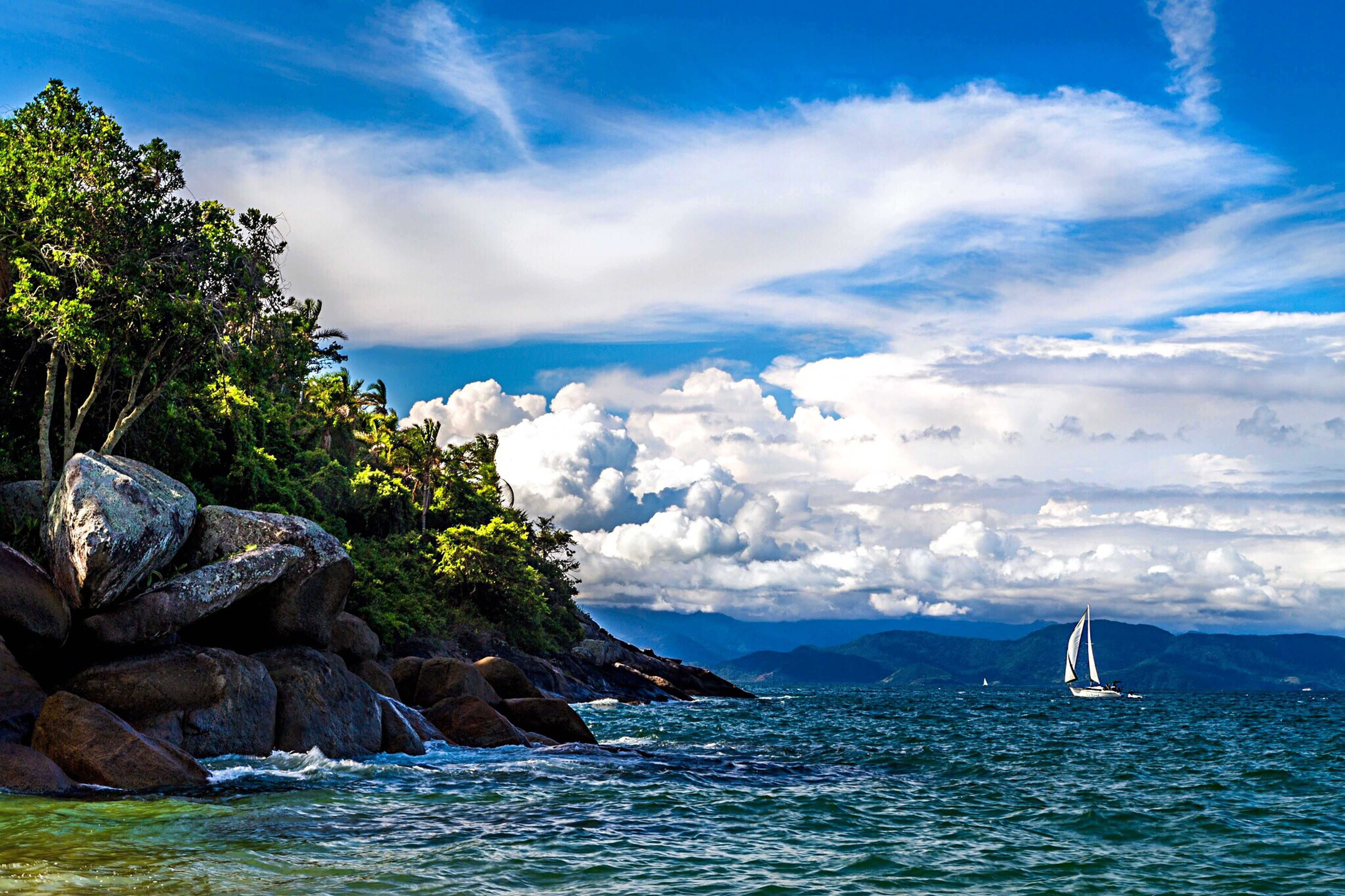 water, sea, sky, waterfront, mountain, scenics, tranquil scene, beauty in nature, transportation, tranquility, cloud - sky, nautical vessel, cloud, nature, mode of transport, blue, mountain range, rock - object, boat, day
