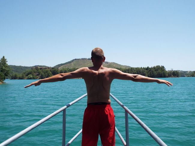 My friend doing the Titanic poseLovely Weather Peace And Quiet People And Places Relaxing Enjoying The Sun Blue Water Blue Sky Blue Wave Blue Travel Destinations Travel Photography Trees Lake Tourist Attraction  Tourism Mountains Hills Tourists People Catamaran Boat Railing Titanic Pose Arms Outstretched Arms Stretched Finding New Frontiers