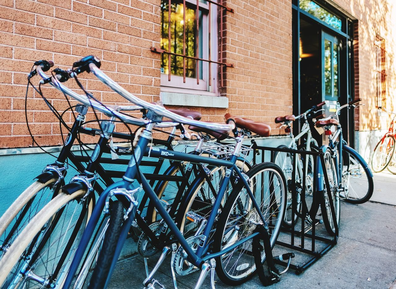 Parked bicycles in front of a bicycle shop in Brooklyn, NY. Bicycle Mode Of Transport Transportation Stationary Land Vehicle Building Exterior Architecture Outdoors Built Structure Bicycle Rack City Day No People Pedal Parked Bicycle Bike