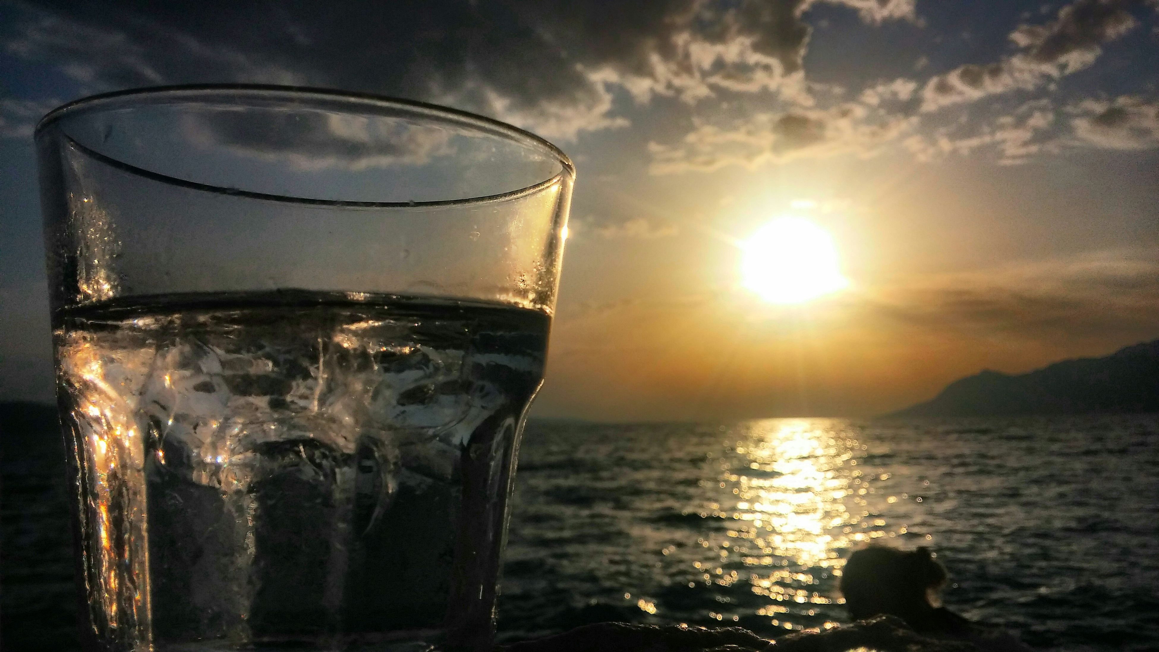 drink, refreshment, food and drink, drinking glass, water, sea, freshness, glass - material, close-up, still life, sky, transparent, table, reflection, alcohol, horizon over water, indoors, sunlight, no people, sunset