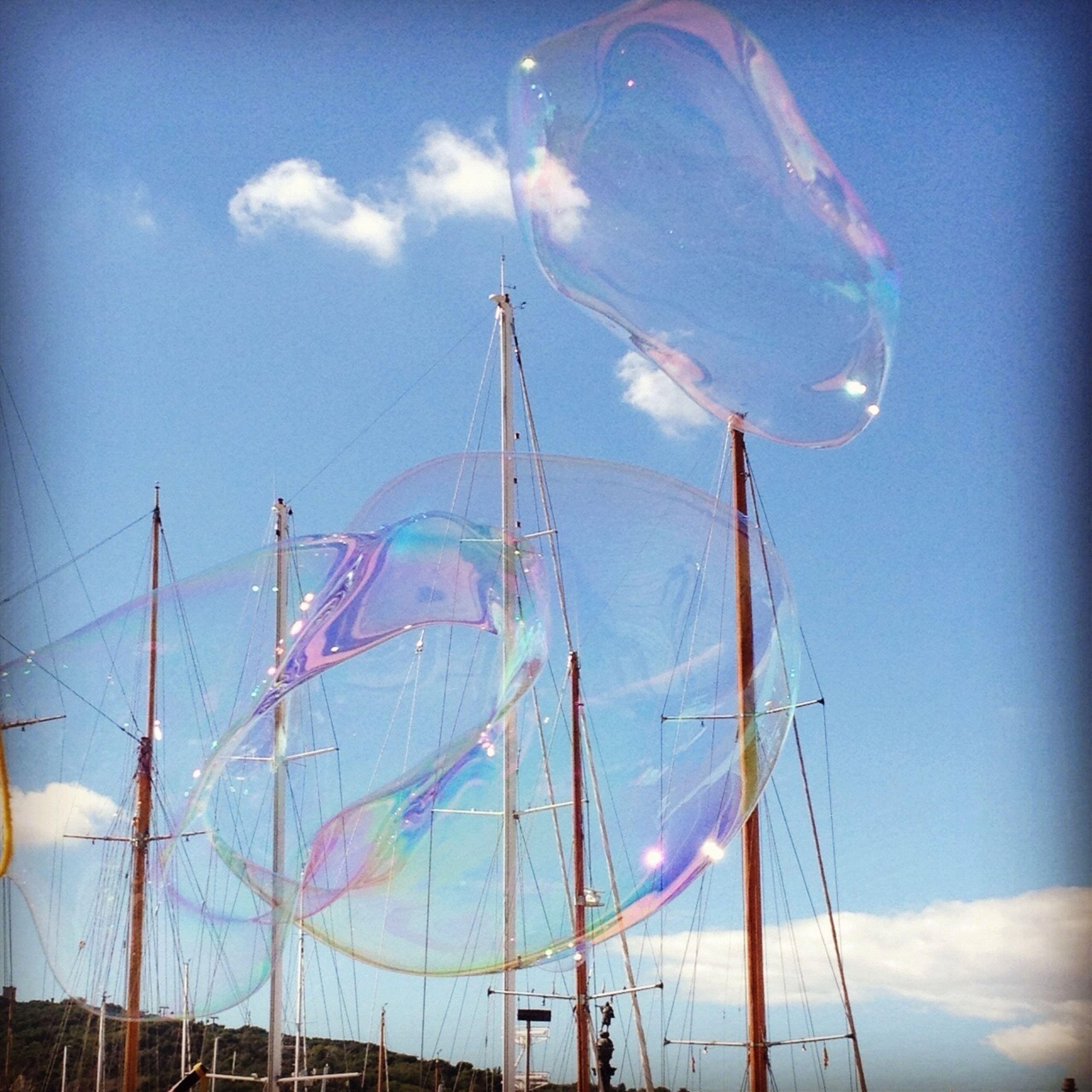 sky, nautical vessel, cloud - sky, low angle view, transportation, amusement park, mode of transport, blue, amusement park ride, boat, mast, cloud, fun, day, outdoors, enjoyment, ferris wheel, arts culture and entertainment, cloudy, rope