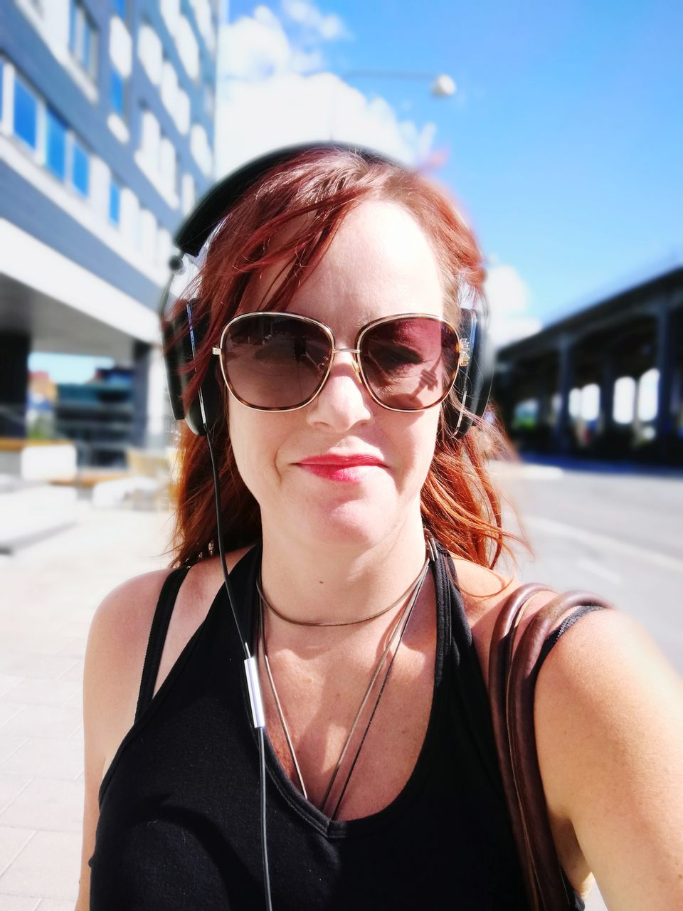 Close-Up Portrait Of Young Woman Wearing Sunglasses And Headphones On Road