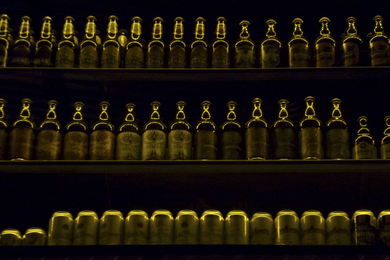 bottle, in a row, shelf, alcohol, order, large group of objects, shelves, indoors, no people, arrangement, repetition, food and drink, wine bottle, abundance, variation, drink, refreshment, liqueur, wine rack, close-up, wine, day