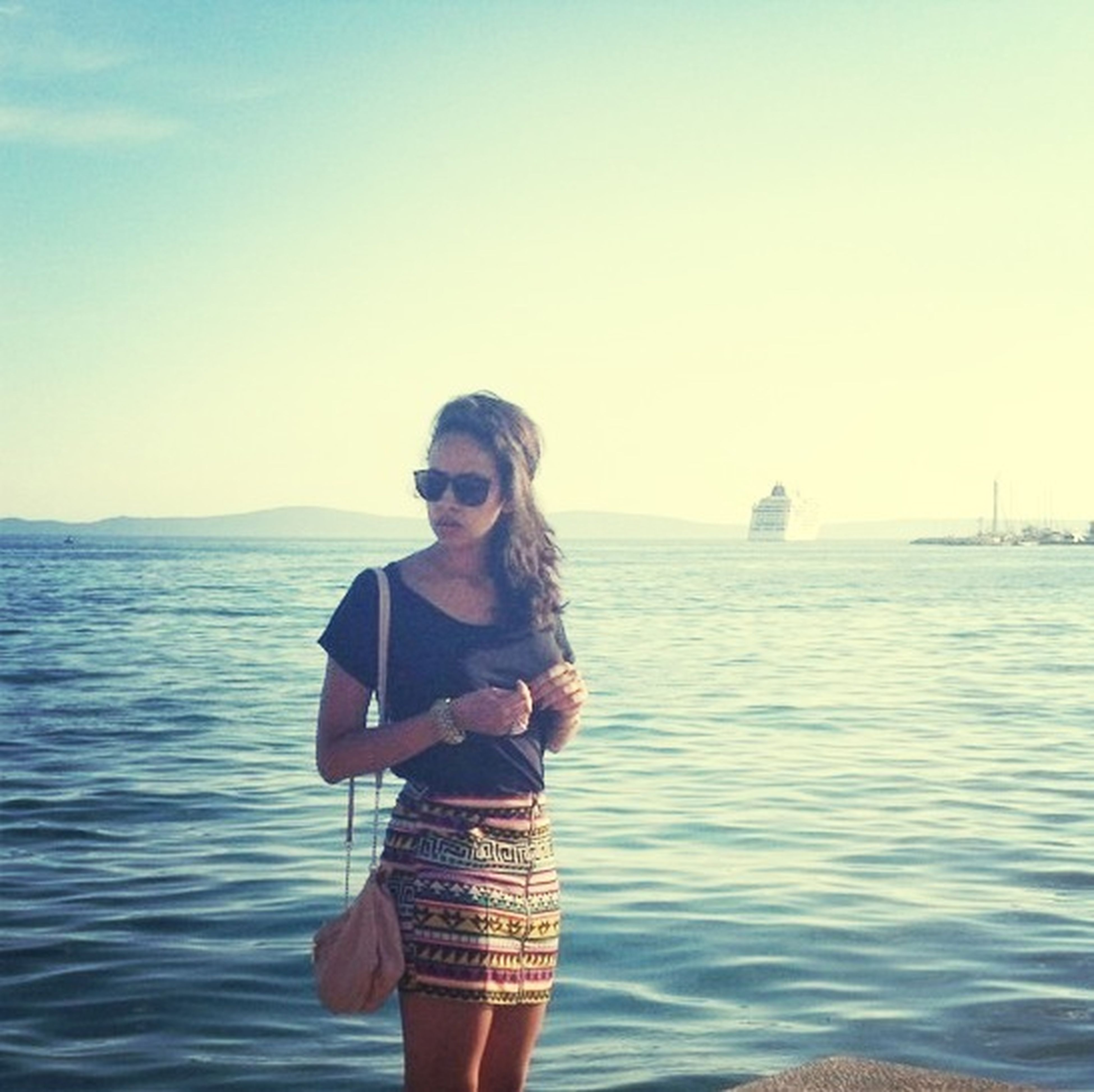 water, sea, lifestyles, leisure activity, young adult, standing, person, clear sky, casual clothing, three quarter length, copy space, waterfront, horizon over water, young women, front view, looking at camera, waist up