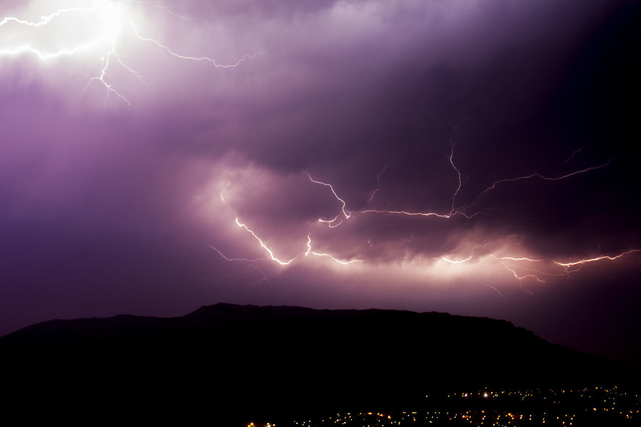 Low Angle View Of Forked Lightning Over Silhouette Mountain