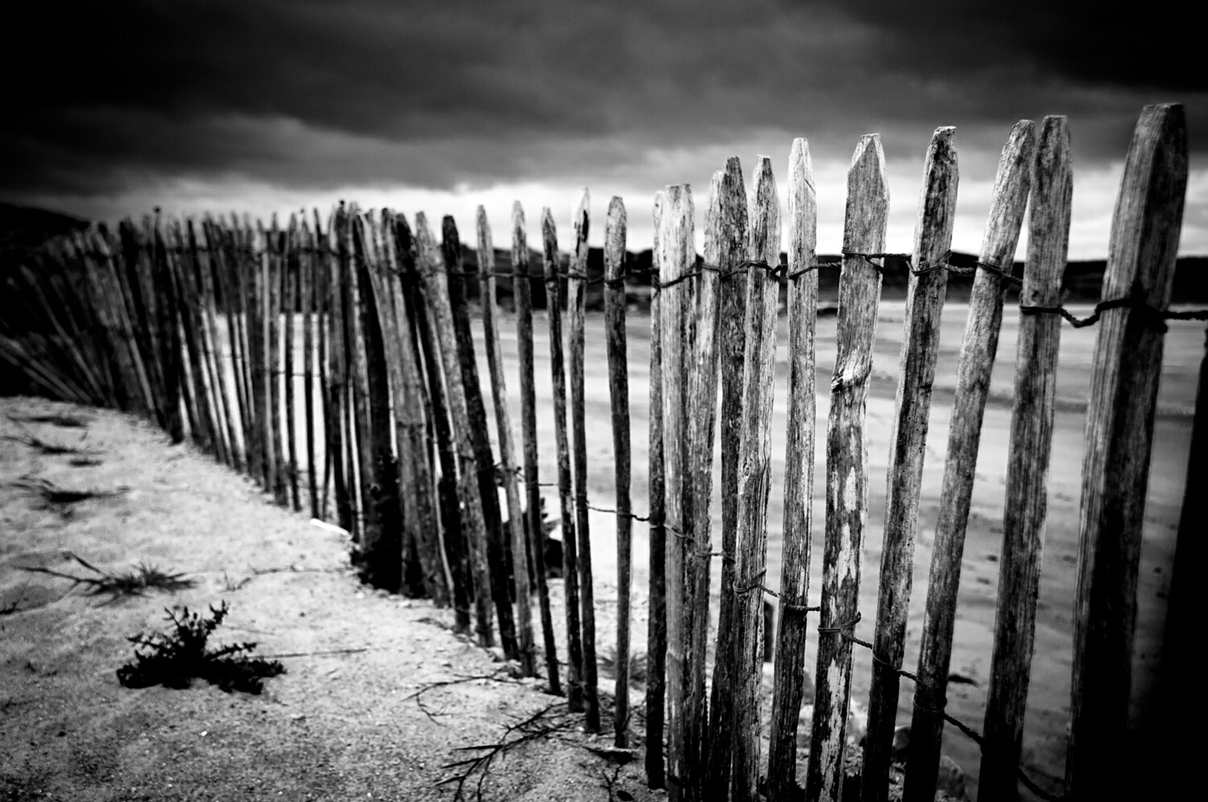 sky, fence, in a row, cloud - sky, wood - material, built structure, protection, architecture, cloudy, safety, the way forward, day, no people, outdoors, security, old, wooden, plant, wooden post, nature