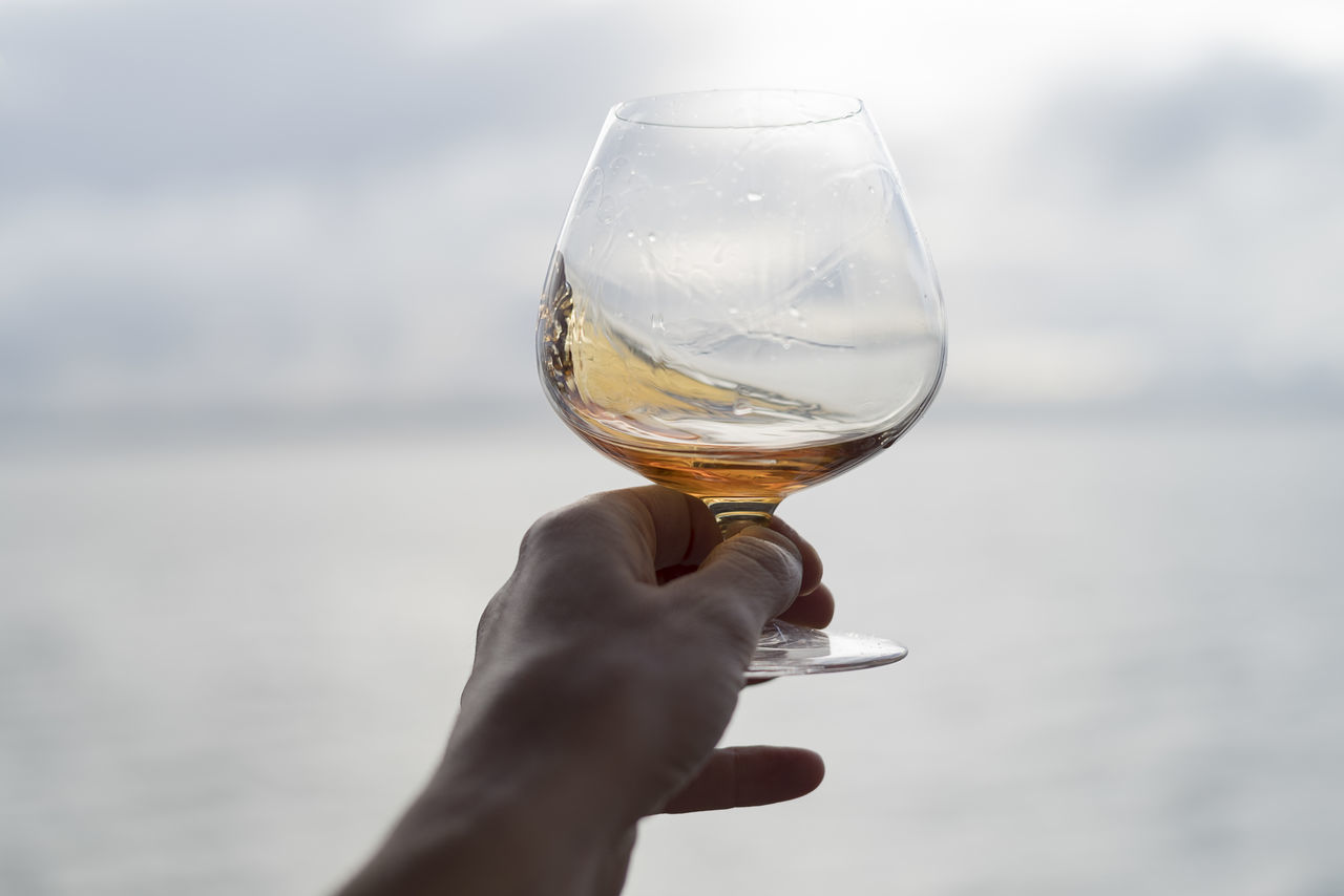 Swirling a snifter of brandy Adult Alcohol Beach Beverage Brandy Close-up Coast, Sand Cognac Day Drink Element Glass Gray Hand Human Masculine Point Of View Scotch Shore Sky Snifter Swirl Tasting Whiskey