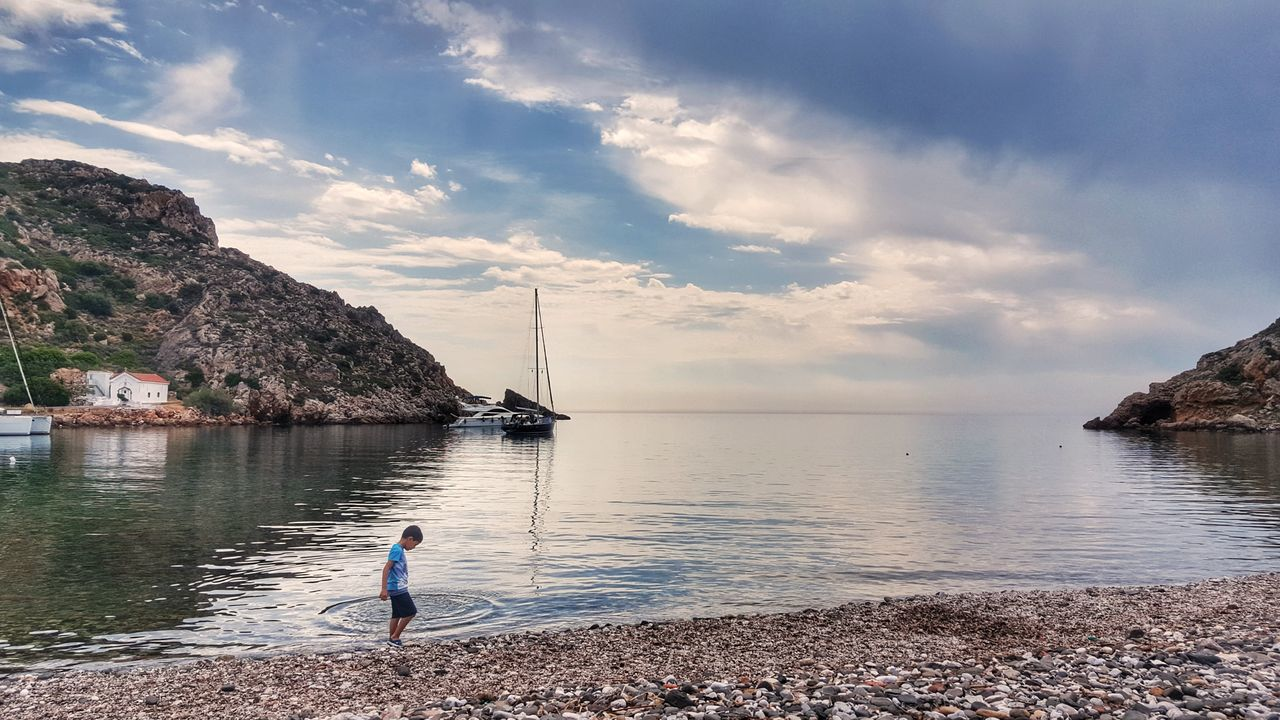 sea, water, sky, nature, one person, beach, rock - object, tranquil scene, tranquility, horizon over water, beauty in nature, scenics, real people, cloud - sky, day, outdoors, full length, people