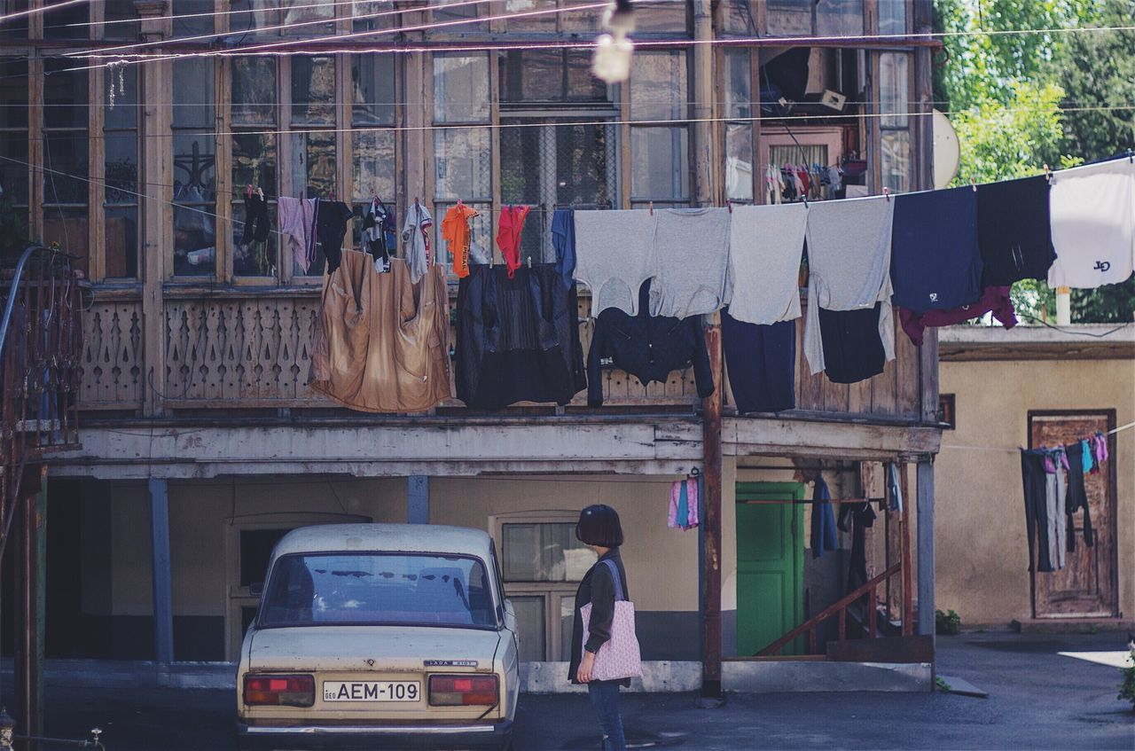 Architecture Architecture Building Exterior Built Structure City Clothing Colors Day Drying Girl Hanging Italian Yards Lifestyles Men Oldstile One Person Outdoors People Real People Retail  Tbilisi VSCO Vscocam Vscofilm Yard