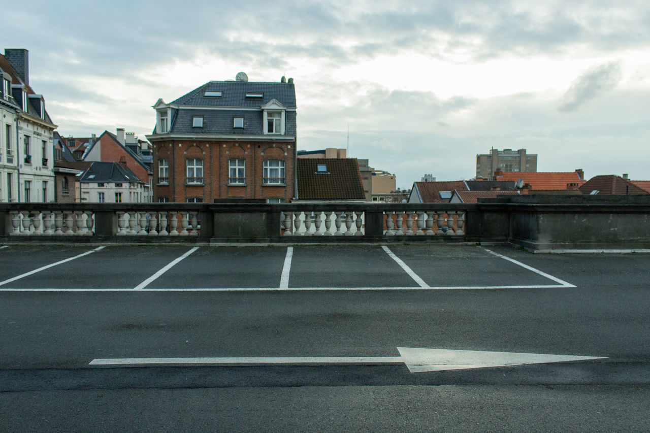 Arrow Symbol In Parking Lot By Buildings In City Against Sky
