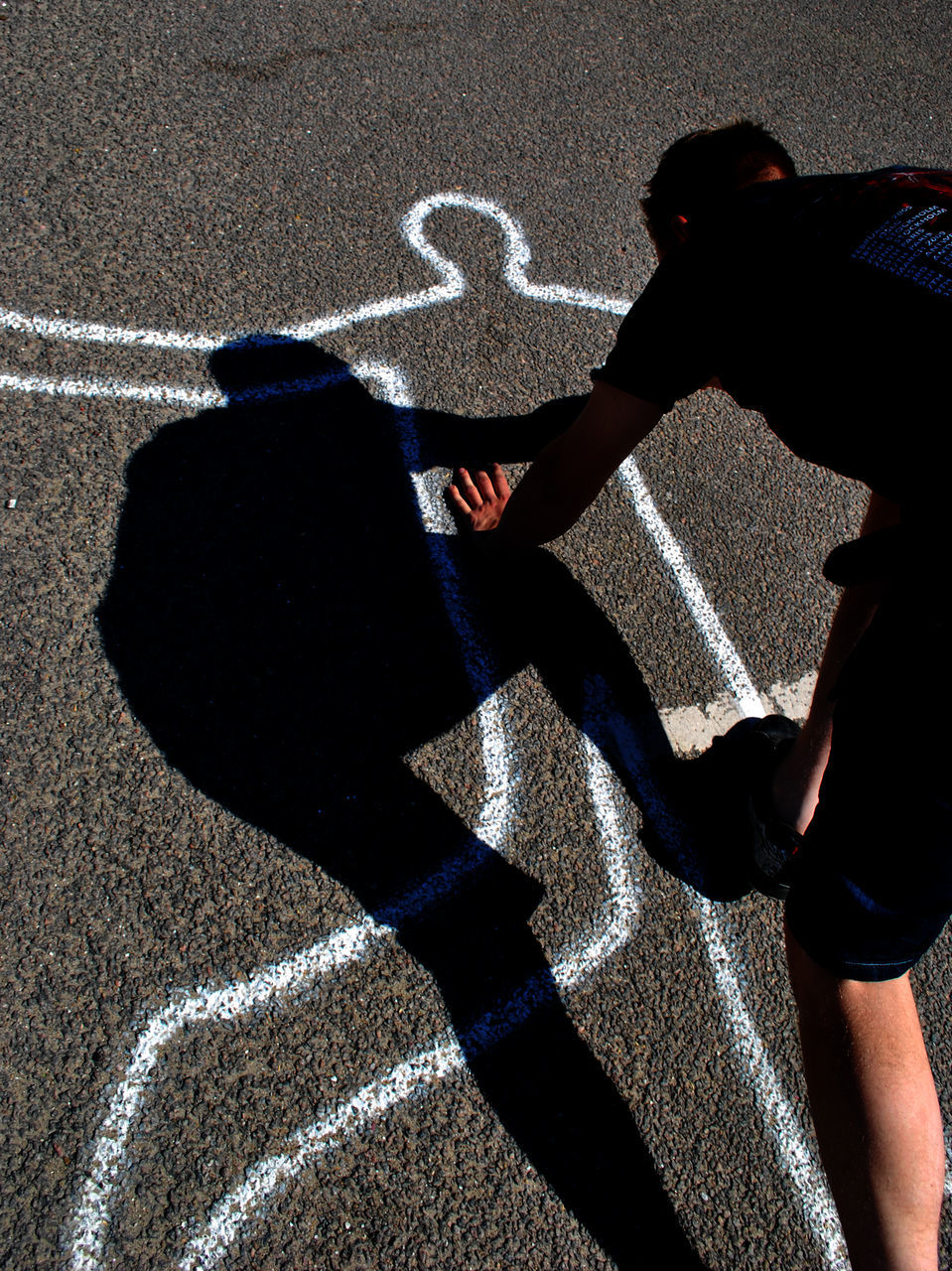shadow, real people, lifestyles, sunlight, one person, leisure activity, asphalt, road, day, high angle view, outdoors, childhood, men, running track, hopscotch, low section, people