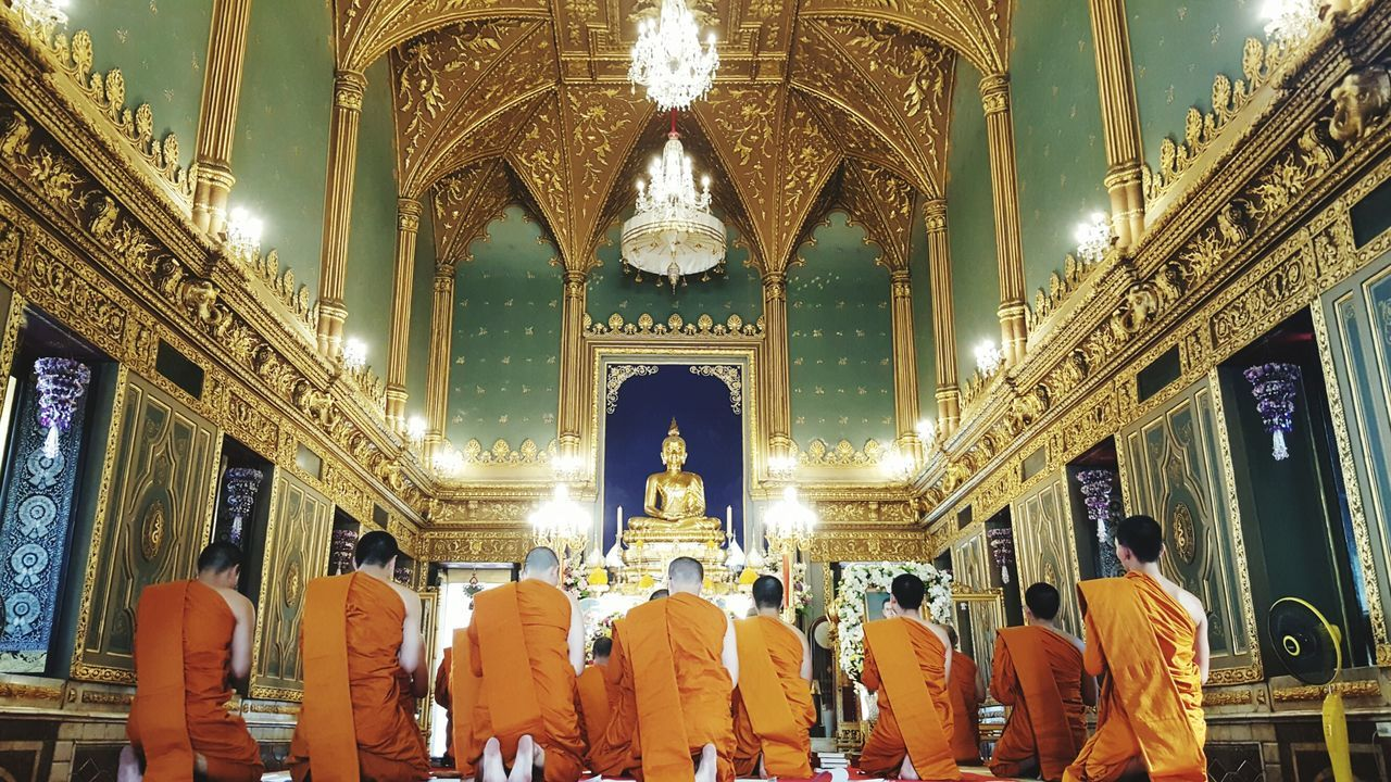 Religion Spirituality Place Of Worship Men Gold Colored Statue Illuminated Indoors  People Salute Sacred Places Temple Architecture Sanctuary  Asian  Asian Culture Travel Destination Meditation Prayer Praying Buddhism Buddhist Temple Buddhist Monks Buddha Statue