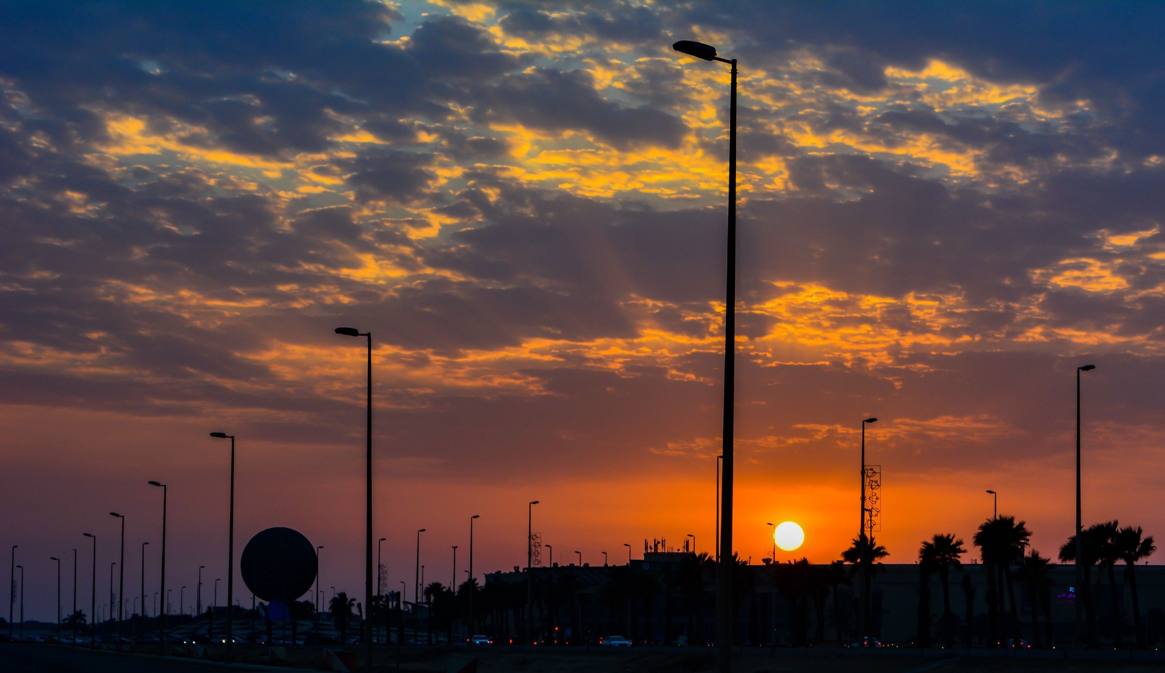 sunset, street light, sky, silhouette, orange color, cloud - sky, transportation, lighting equipment, beauty in nature, in a row, car, scenics, nature, dramatic sky, cloud, cloudy, tranquility, low angle view, tree, illuminated