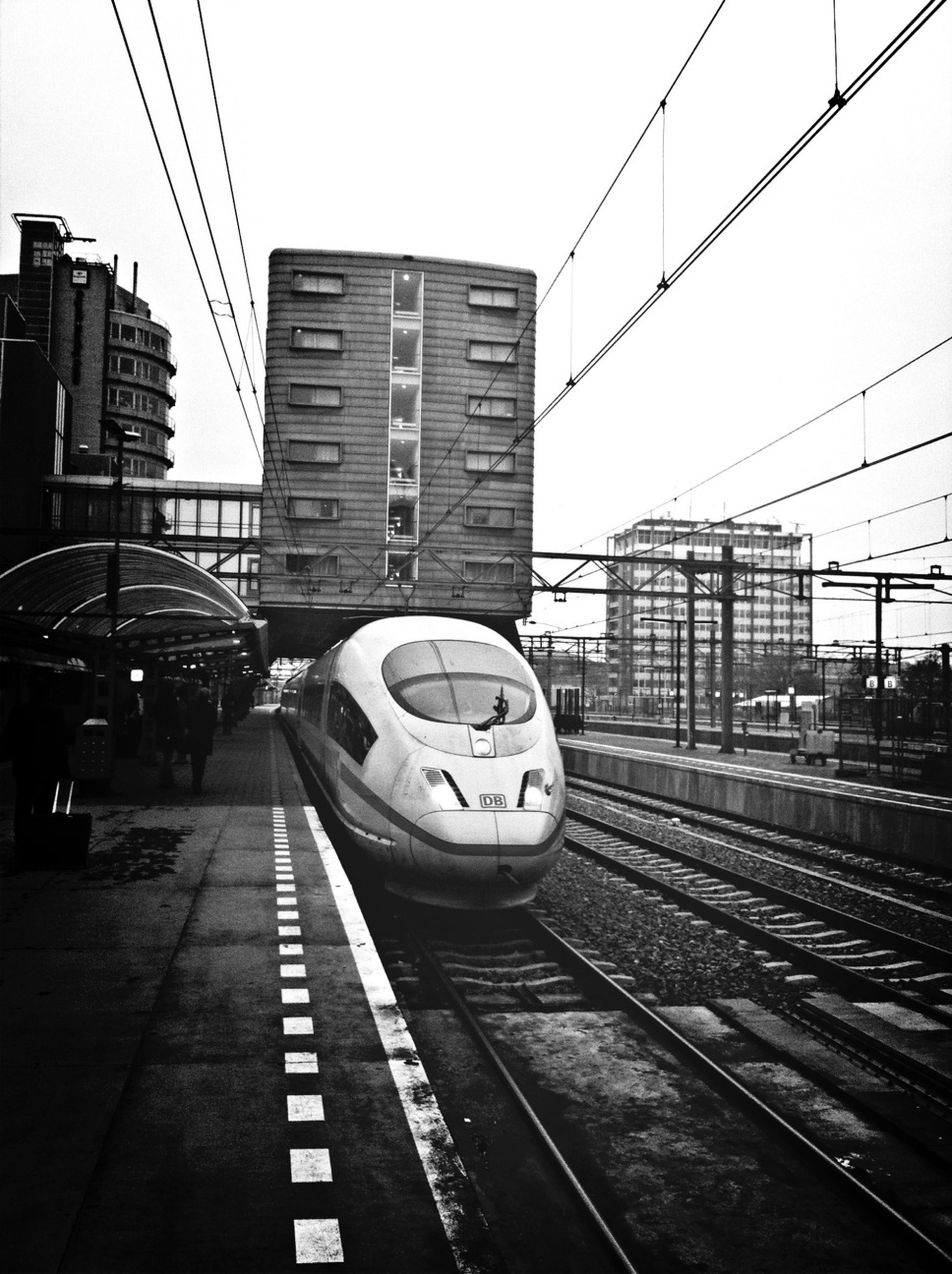transportation, railroad track, public transportation, rail transportation, railroad station, architecture, built structure, railroad station platform, city, building exterior, mode of transport, clear sky, train - vehicle, travel, city life, connection, train, public transport, passenger train, on the move