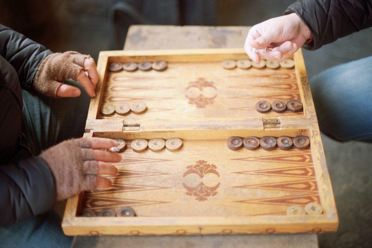 Cropped Image Of Men Playing Board Game