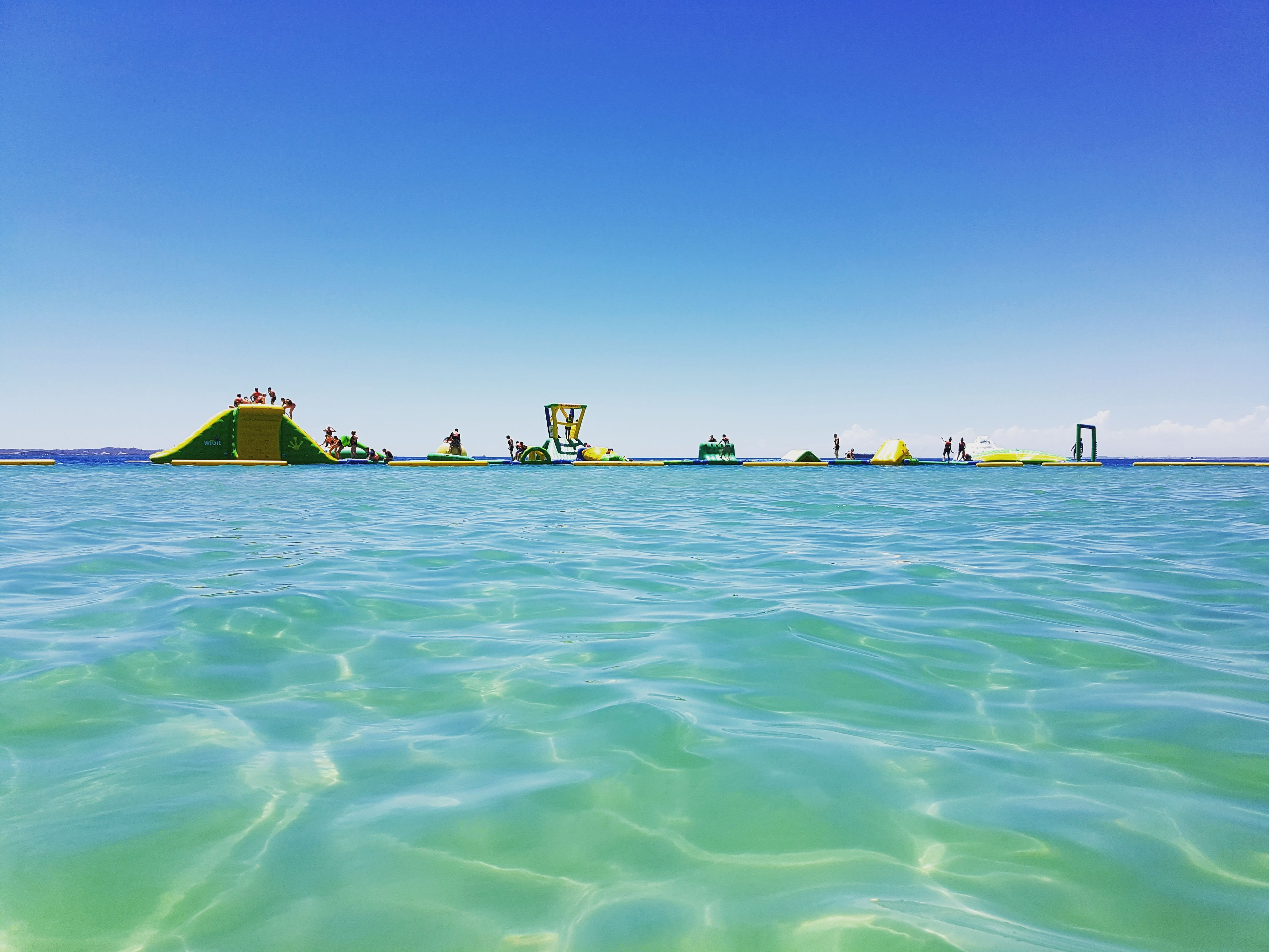 sea, blue, water, clear sky, scenics, nature, tranquility, sunlight, beach, beauty in nature, tranquil scene, day, sky, outdoors, vacations, no people, sand, architecture, horizon over water