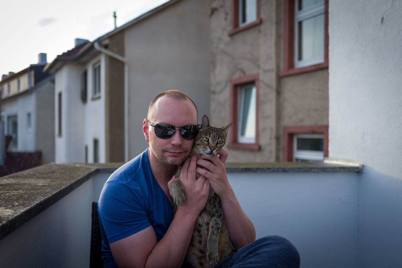 A cat and her man Architecture Building Exterior Built Structure Day Front View House Lifestyles Looking At Camera Mammal Man One Person Outdoors Portrait Real People Savannah Savannah Cat  Smiling Sunglasses Sunglasses :) Young Adult