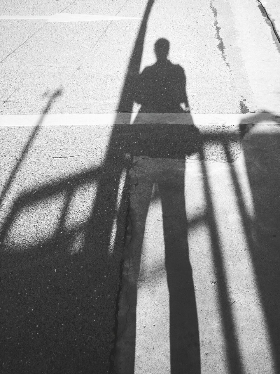 shadow, focus on shadow, sunlight, real people, long shadow - shadow, leisure activity, one person, outdoors, lifestyles, day, high angle view, silhouette, standing, men, full length, people