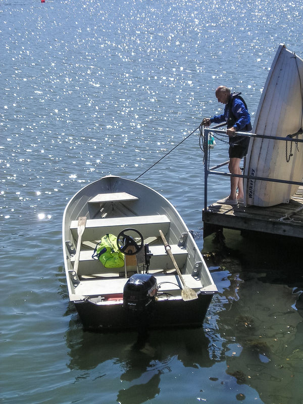 A man ties up his motorboat. Beauty In Nature Day Dinghy Horizon Over Water Lifestyles Men Motorboat Nature Nautical Vessel One Person Outboard Engine Outboard Motor Outdoors People Pontoon Real People River Rope Sea Sky Transportation Water Waterfront