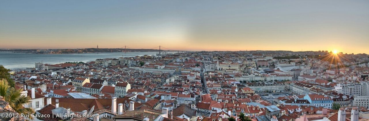 sunset, cityscape, architecture, building exterior, crowded, city, high angle view, outdoors, built structure, town, sea, travel destinations, sky, roof, nature, horizon over water, day, people