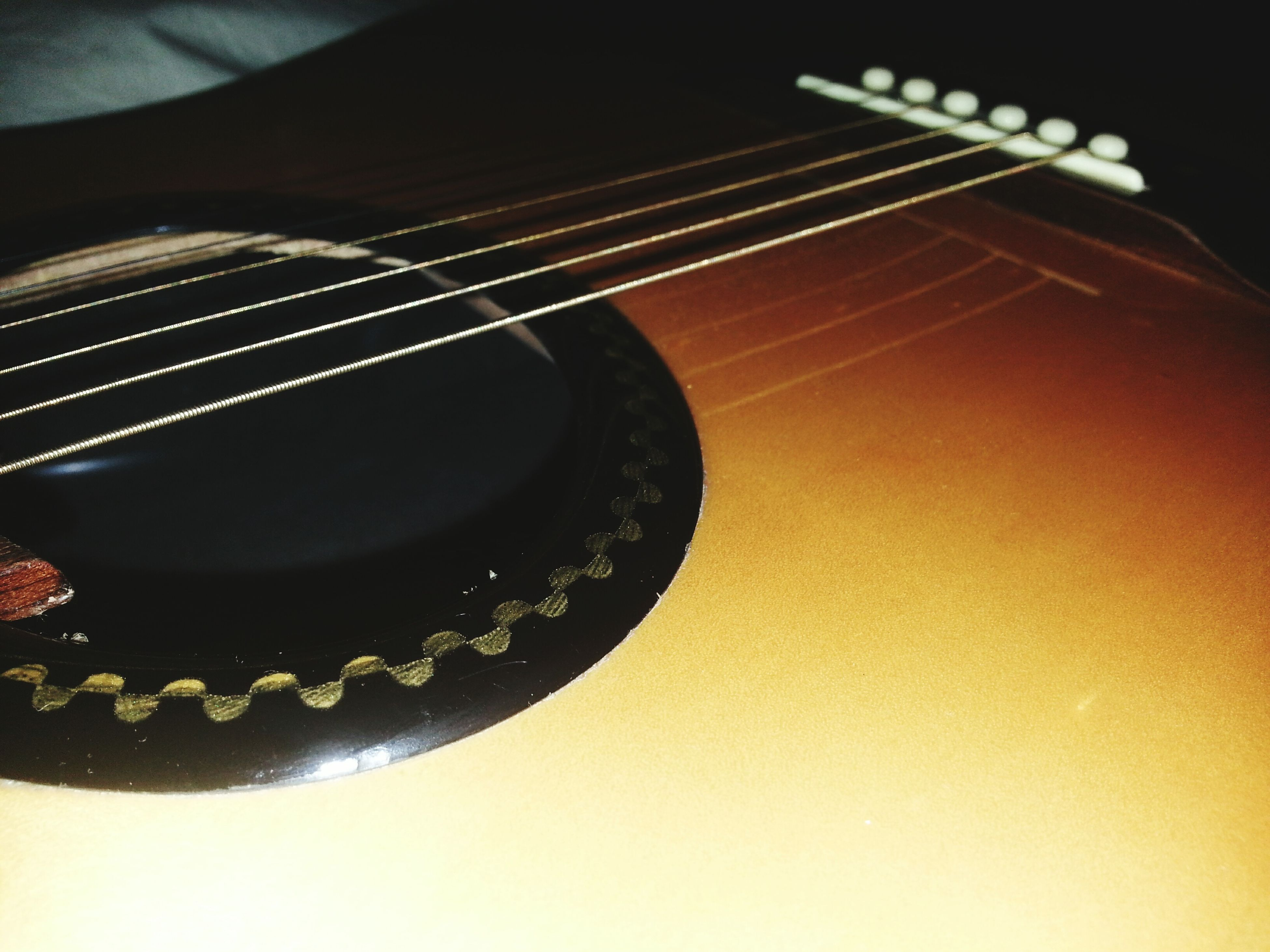indoors, still life, close-up, music, high angle view, musical instrument, single object, table, musical instrument string, arts culture and entertainment, musical equipment, studio shot, no people, guitar, technology, acoustic guitar, black color, string instrument, part of, selective focus